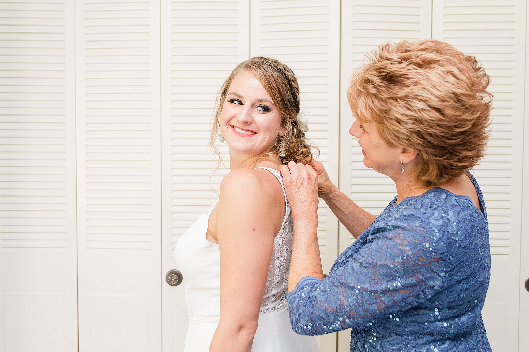 mother of bride helps with wedding dress