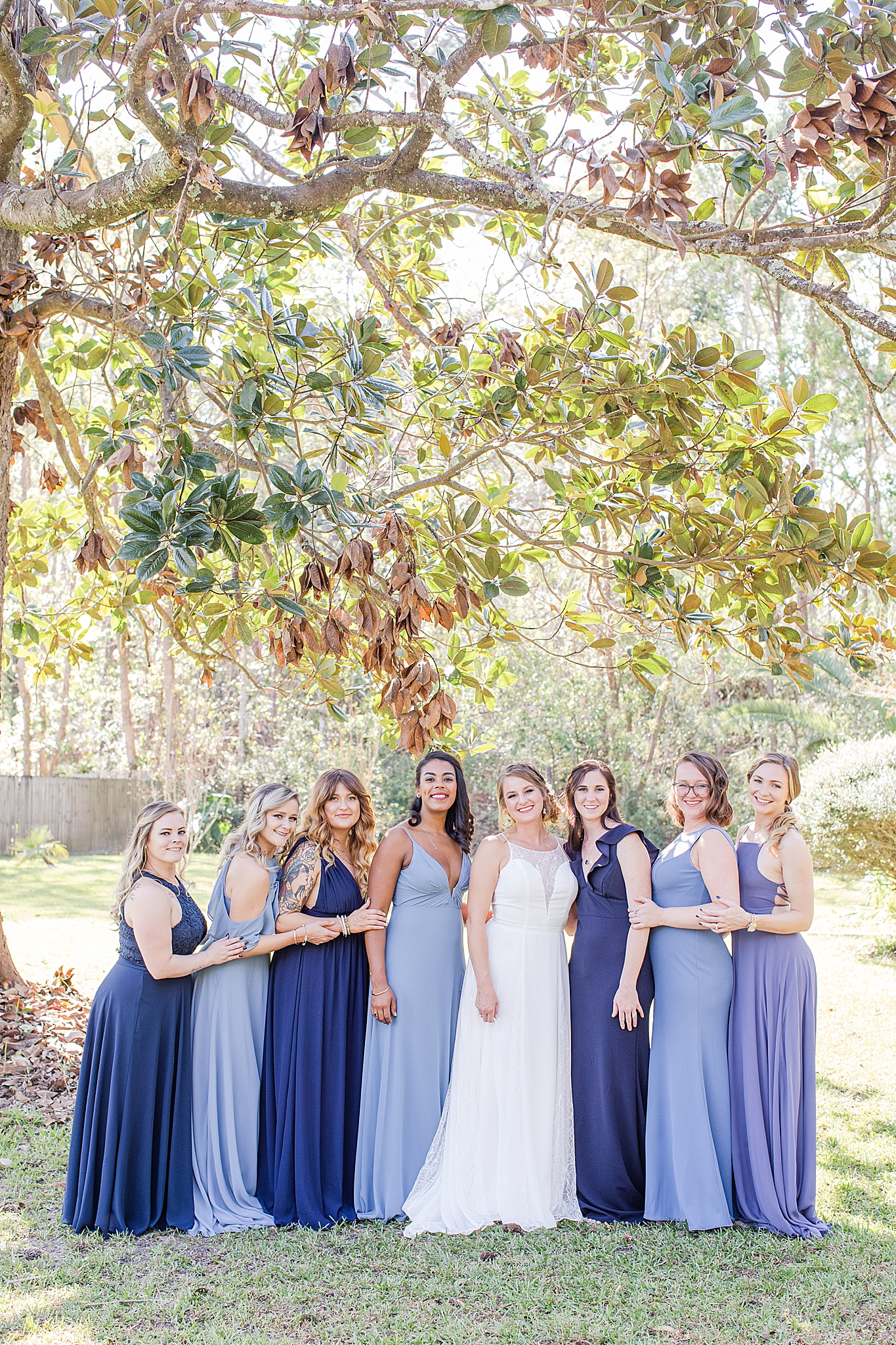 bride poses with bridesmaids in blue gowns
