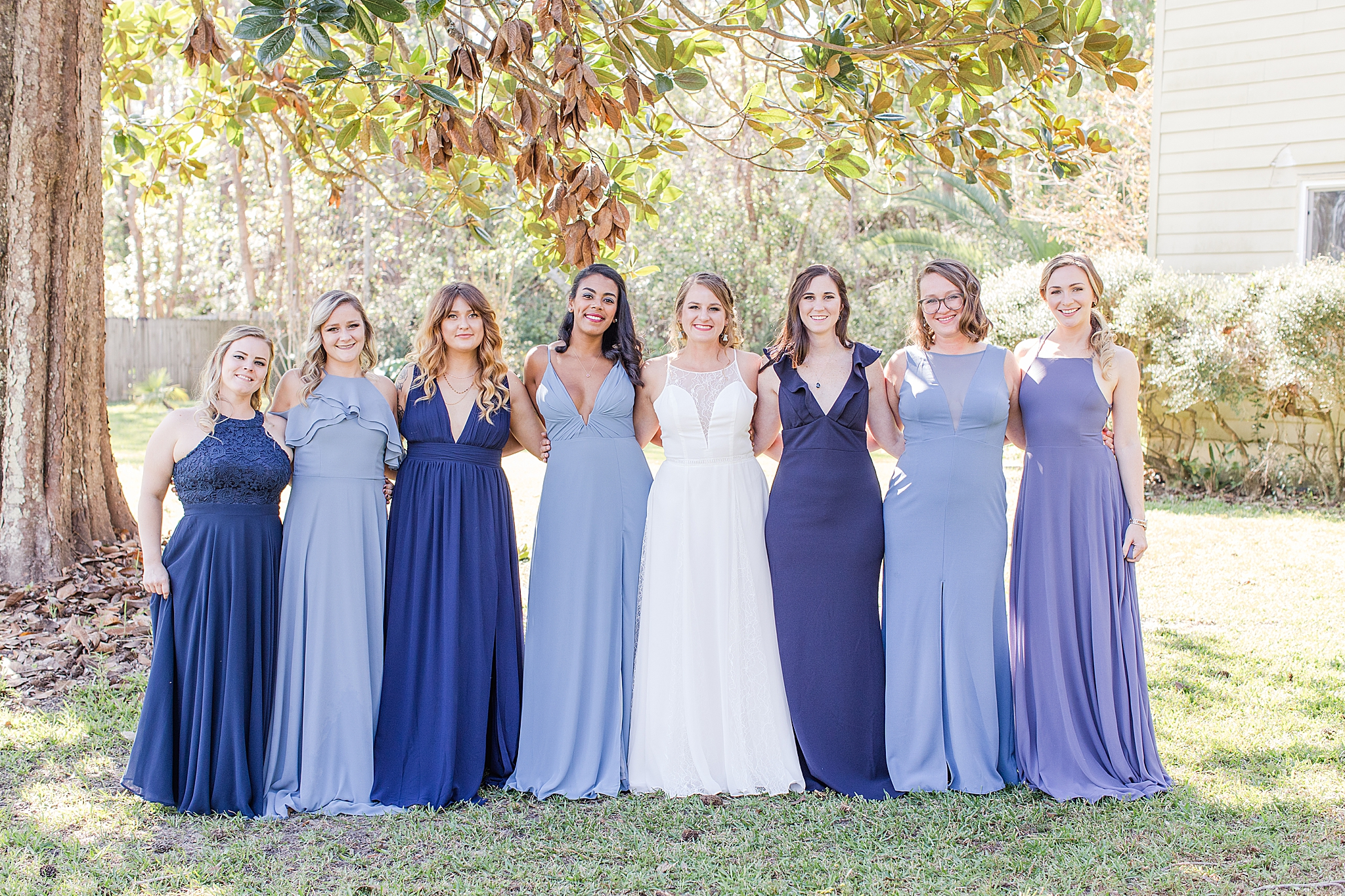 bridesmaids in mismatched blue gowns hug bride