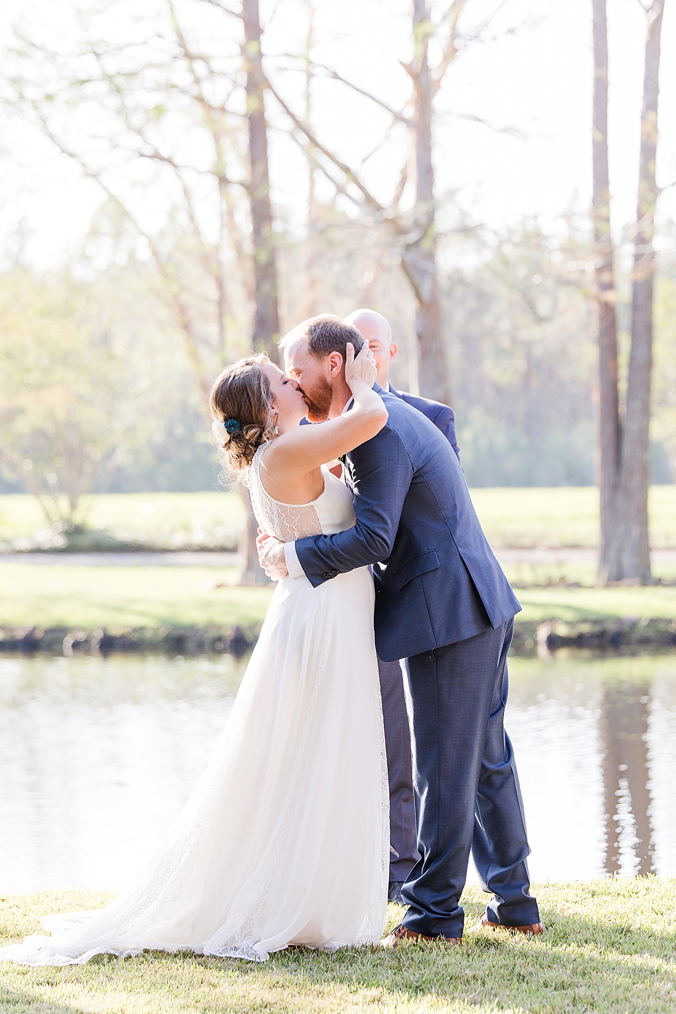 bride and groom kiss during wedding ceremony at Burkhardt Pond