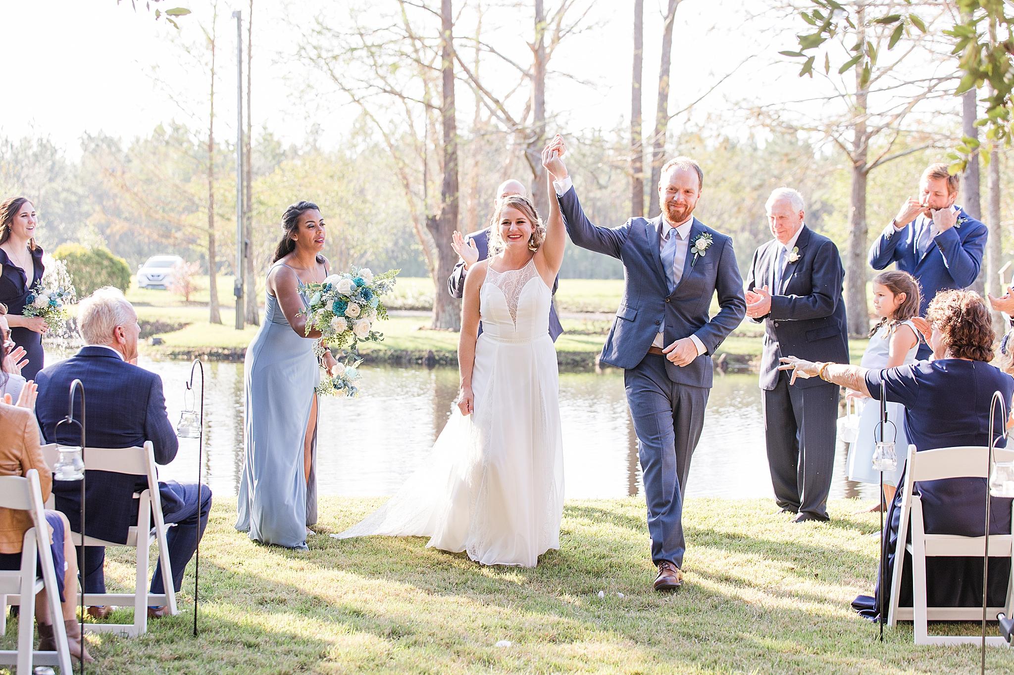 newlyweds walk up aisle at Burkhardt Pond