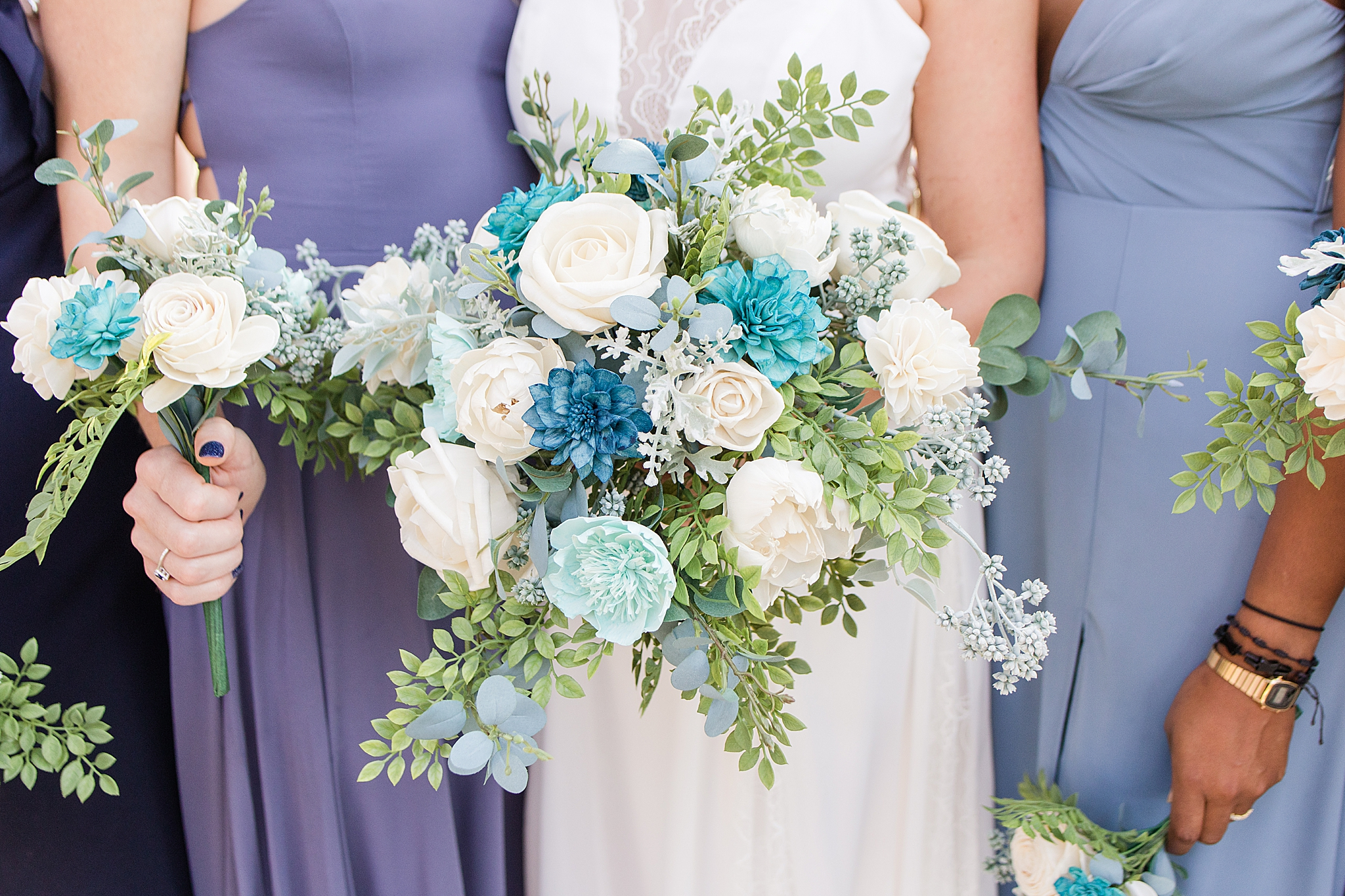bride holds bouquet of blue and white flowers