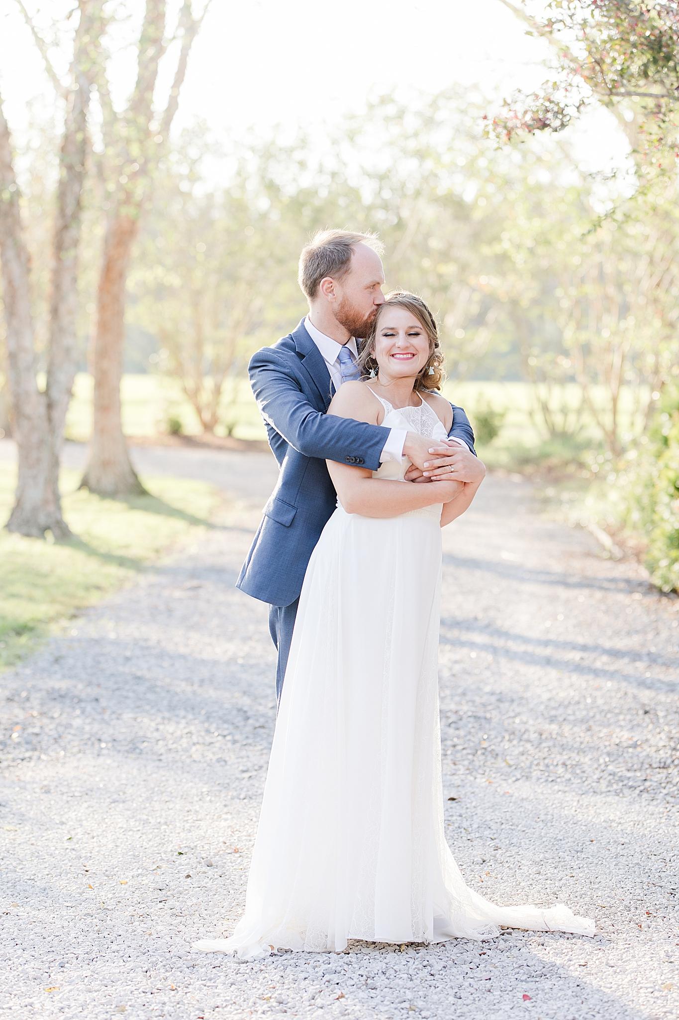 groom kisses bride on head during wedding photos at Burkhardt Pond