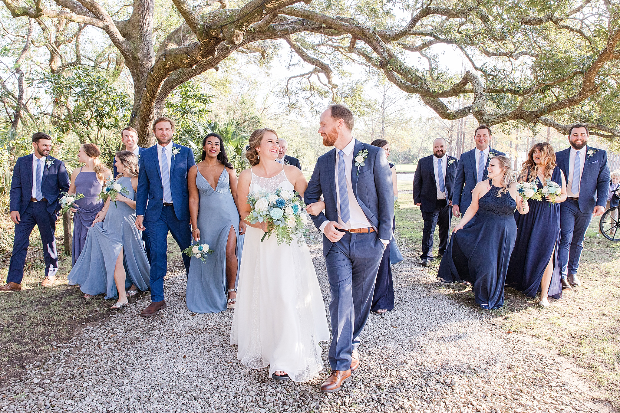 wedding party walks with bride and groom after Burkhardt Pond wedding