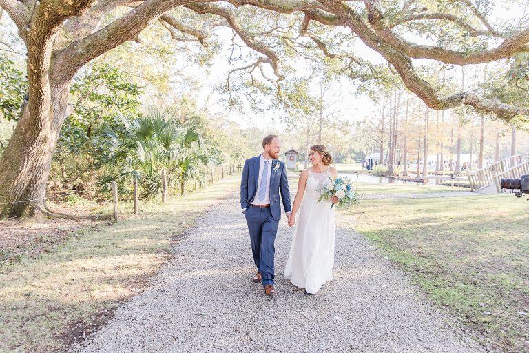 bride and groom walk through Burkhardt Pond