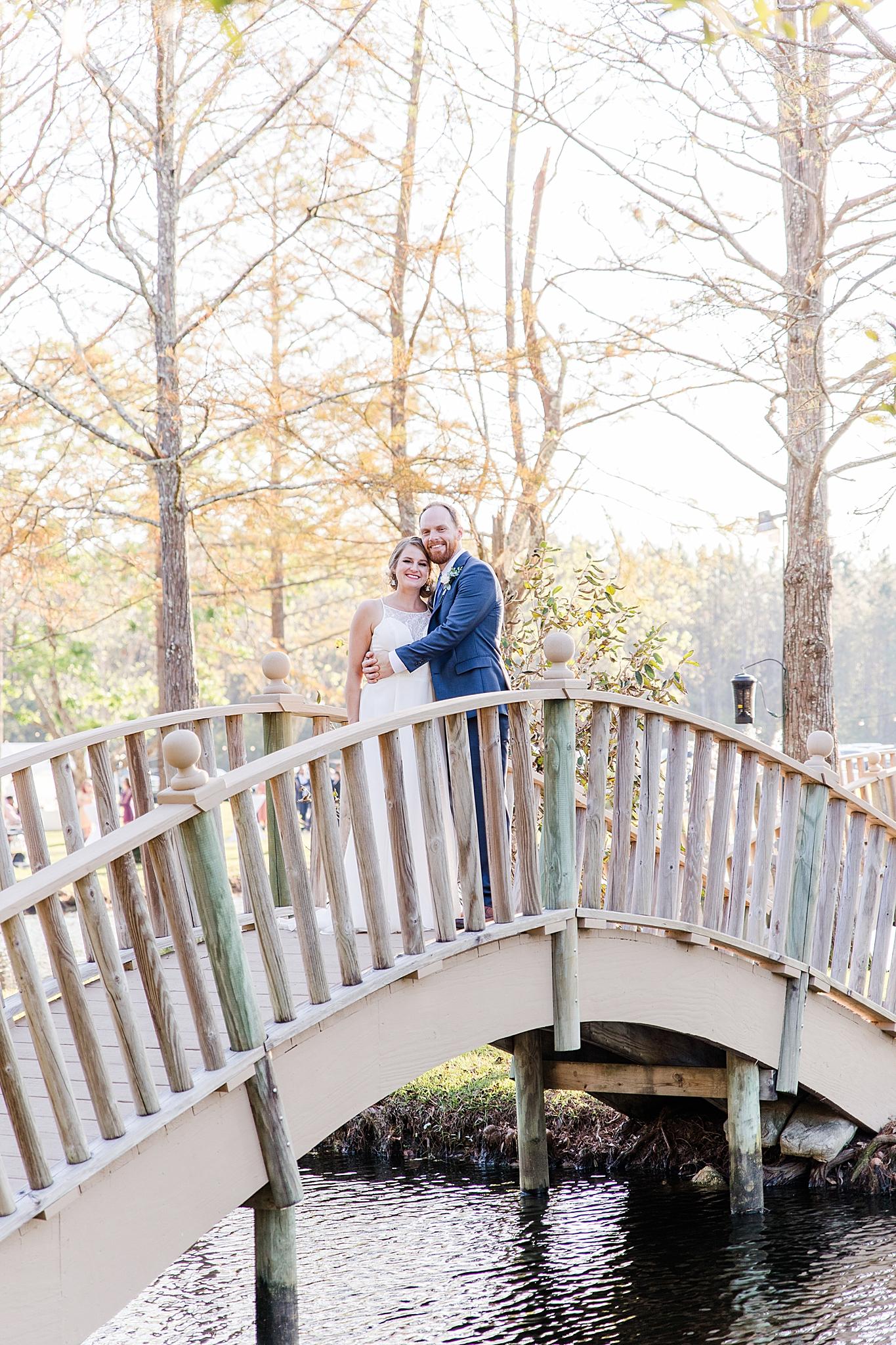 newlyweds stand on bridge at Burkhardt Pond