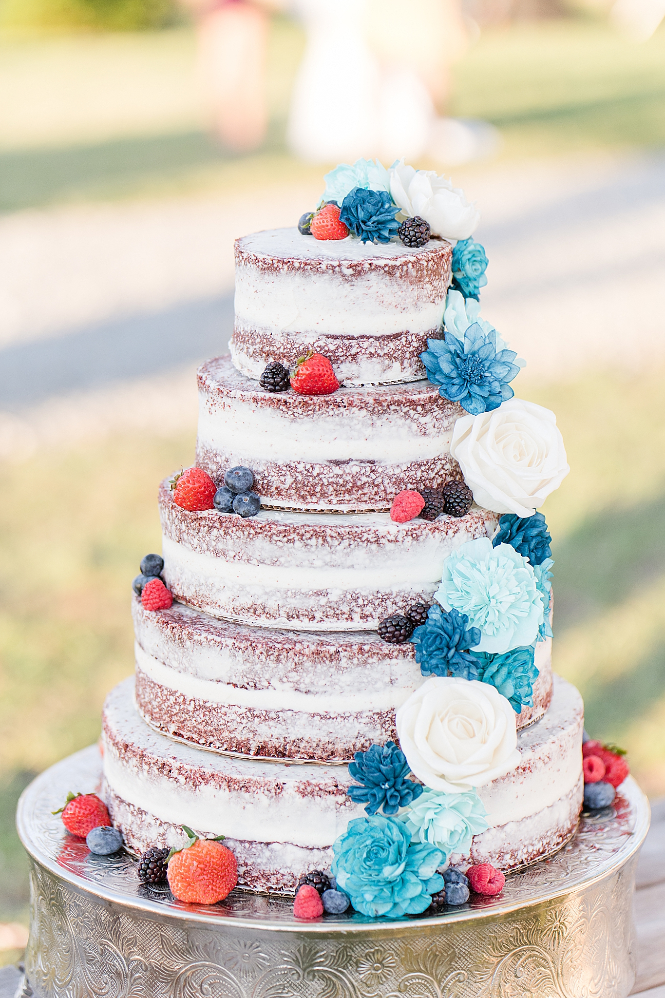 naked cake with fruit and blue flower accents