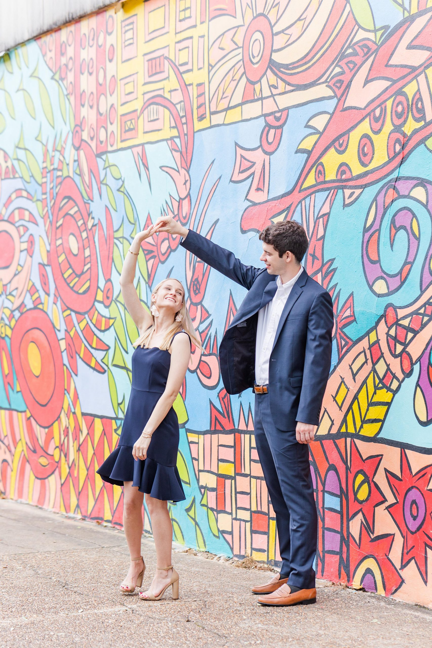 bride and groom dance in front of colorful mural
