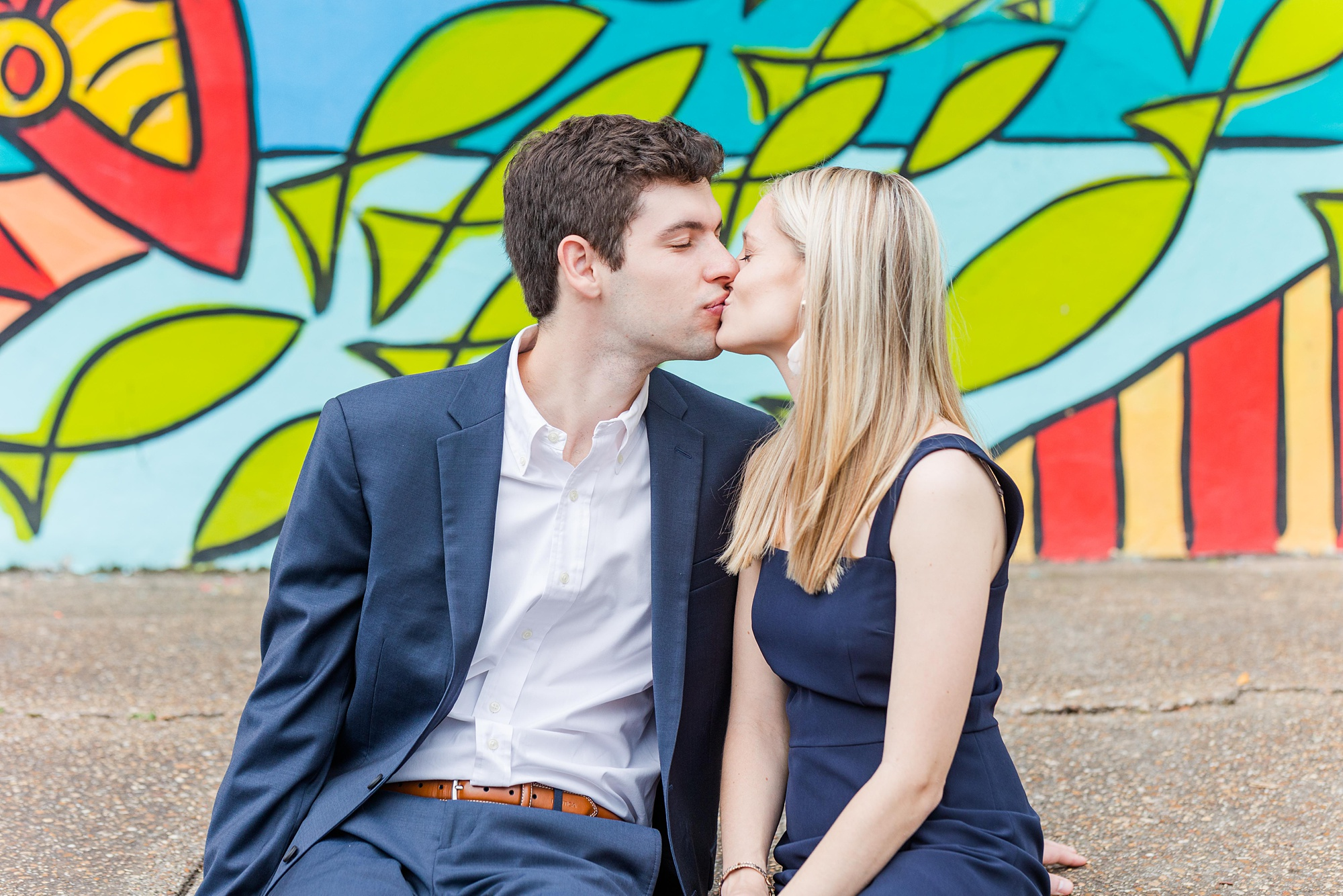 bride and groom pose in front of colorful mural in Downtown Fairhope