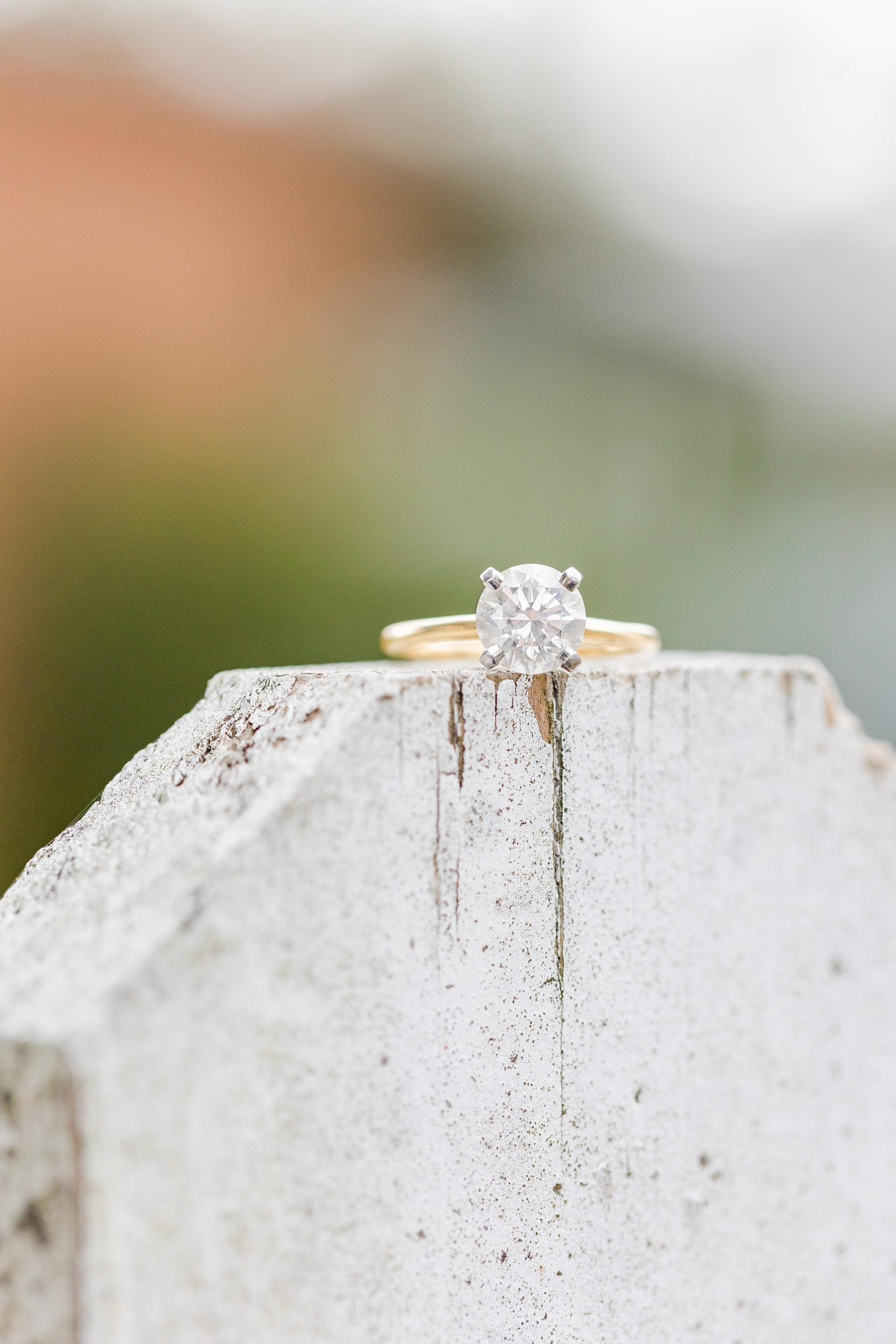 engagement ring rests on concrete slab during engagement photos