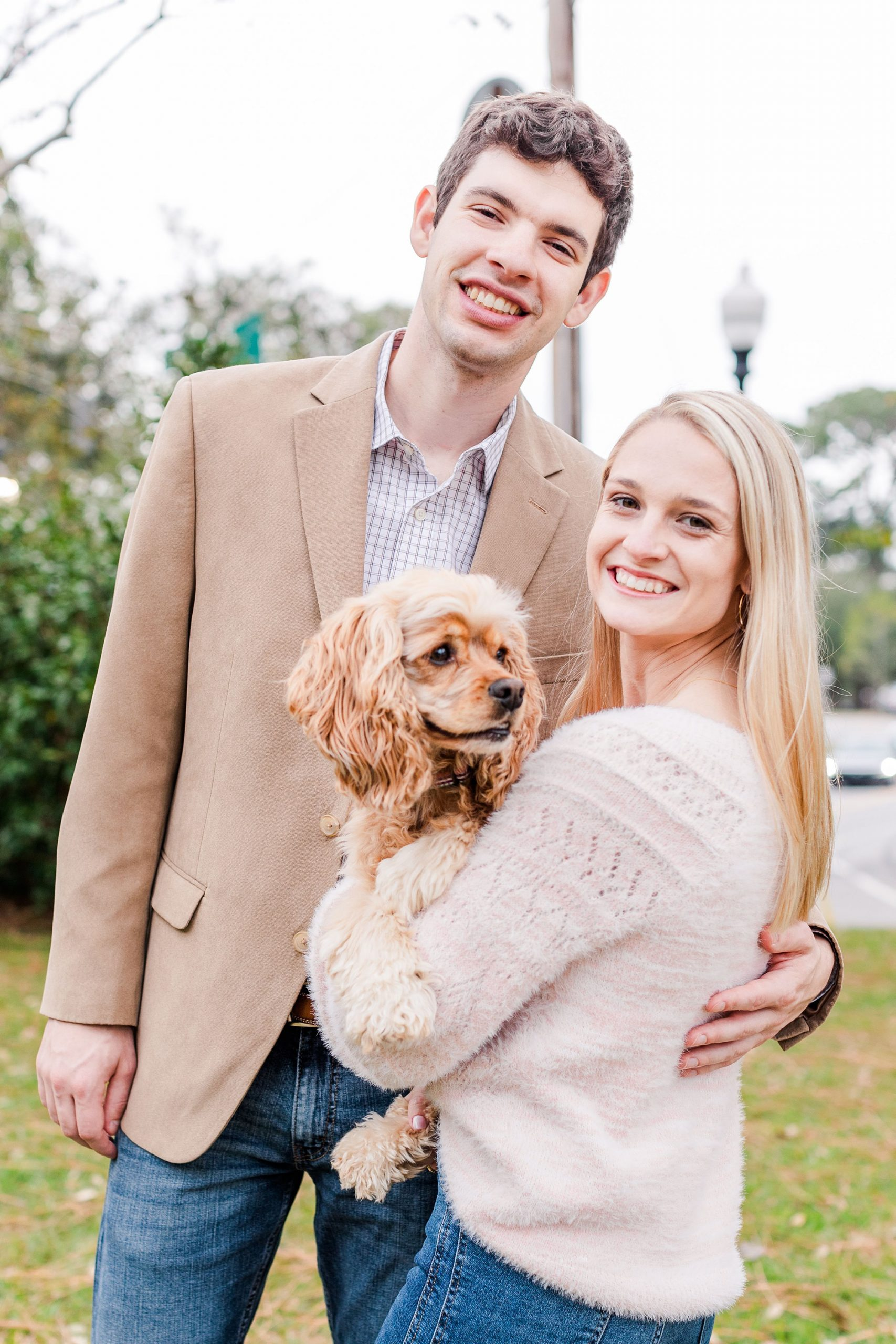 engaged couple poses with cocker spaniel during Mobile Bay engagement session