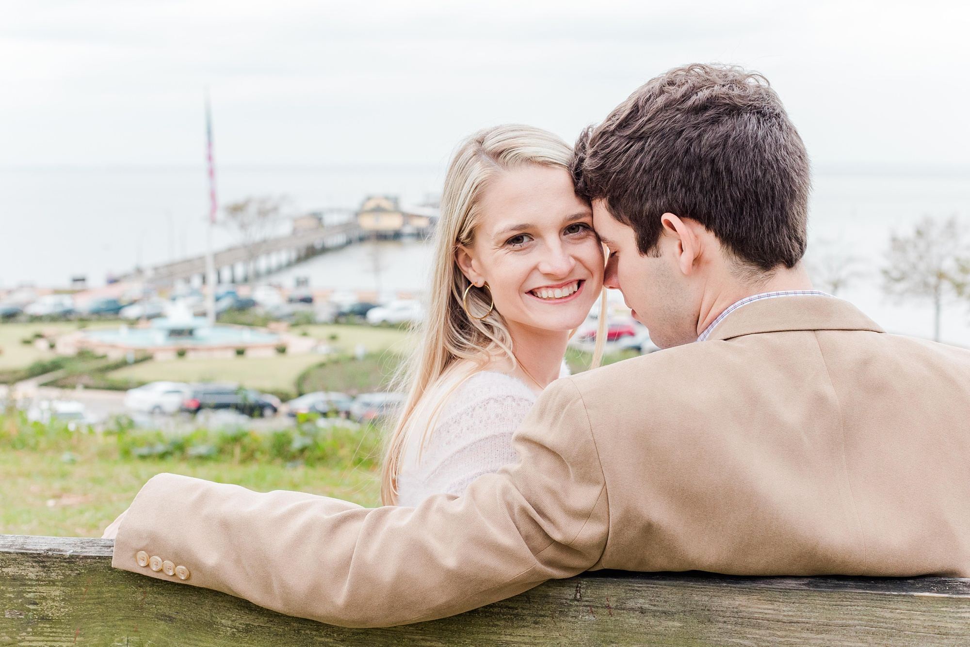 groom looks at bride sitting on bench overlooking Mobile Bay