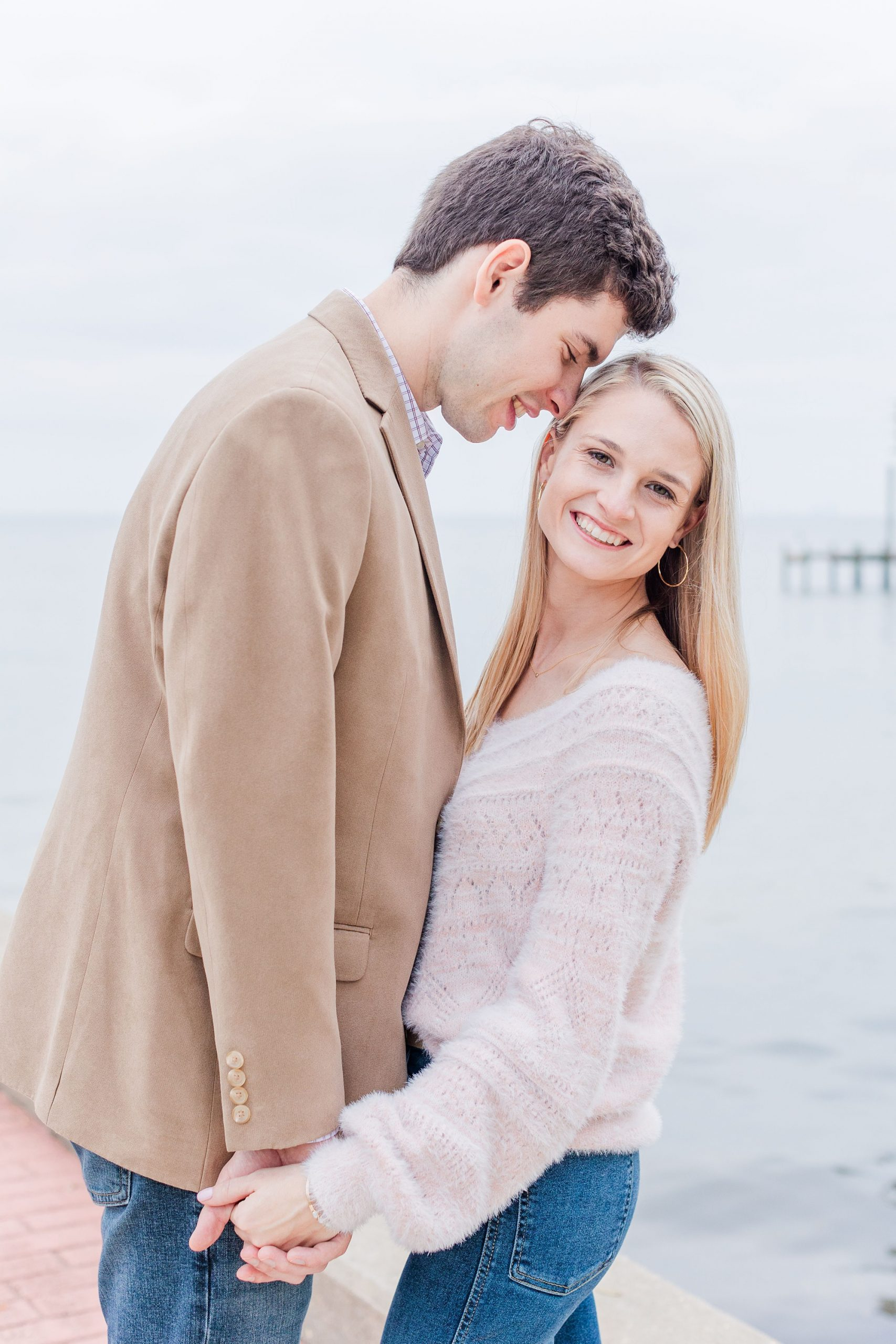 groom nuzzles bride during AL engagement portraits along Mobile Bay