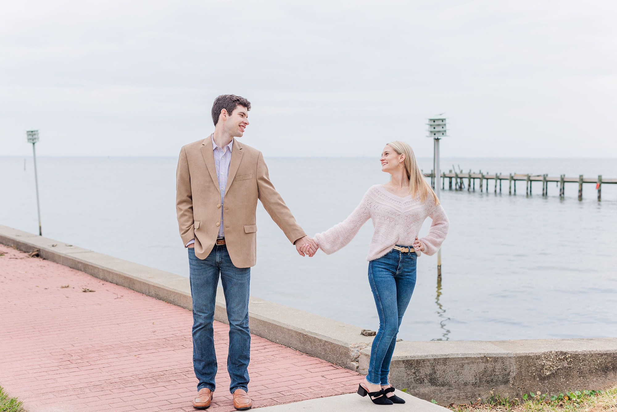 bride and groom pose by Mobile Bay waterfront