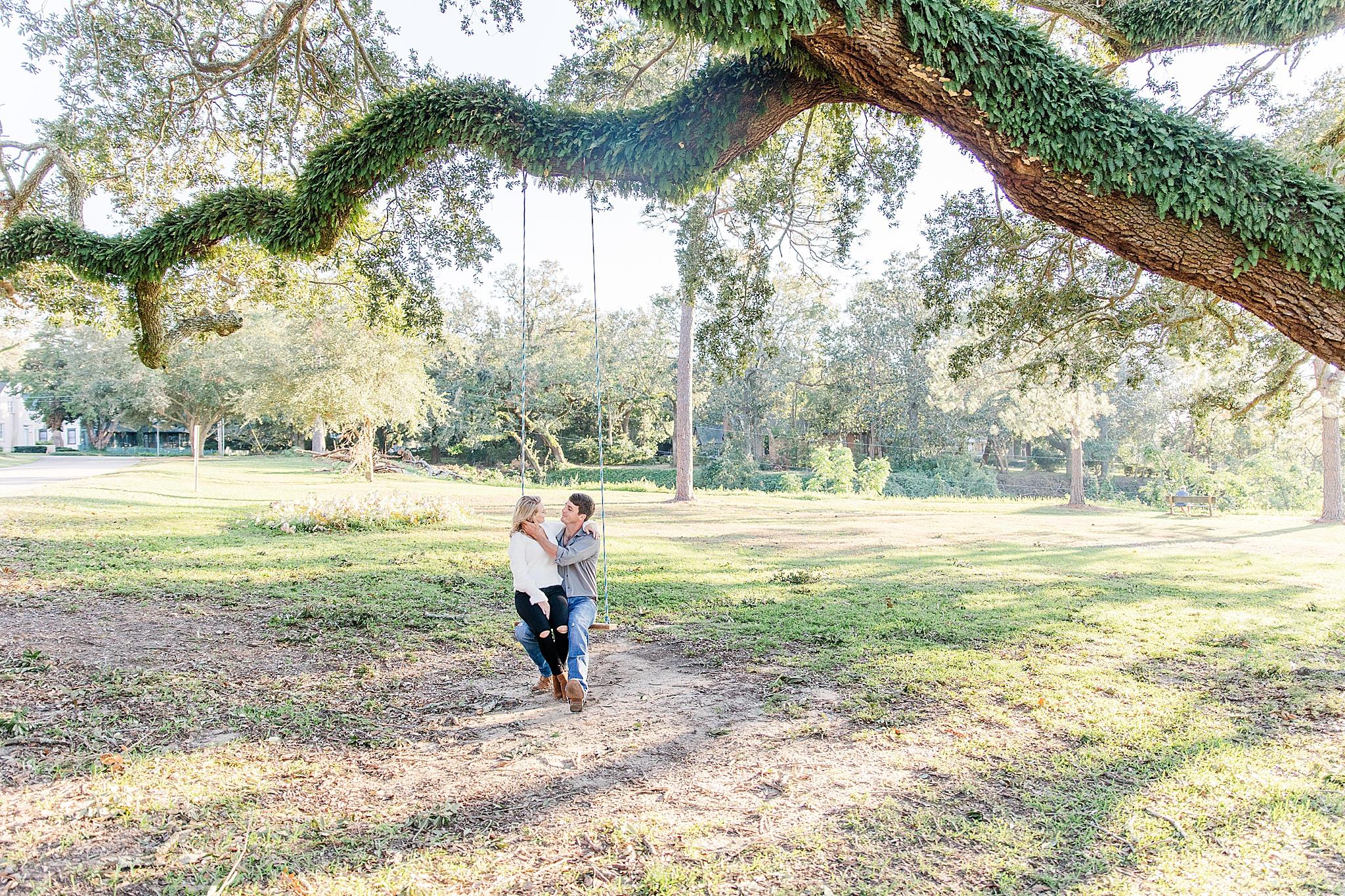 bride and groom sit on wooden swing in Fairhope AL park