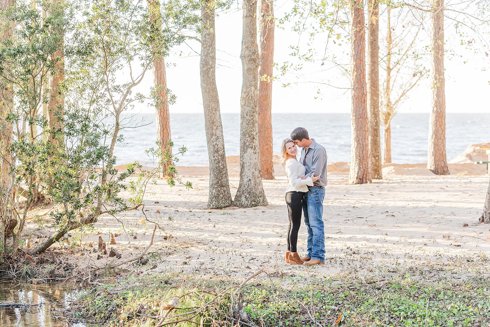 bride and groom pose in clearing at Fairhope AL park