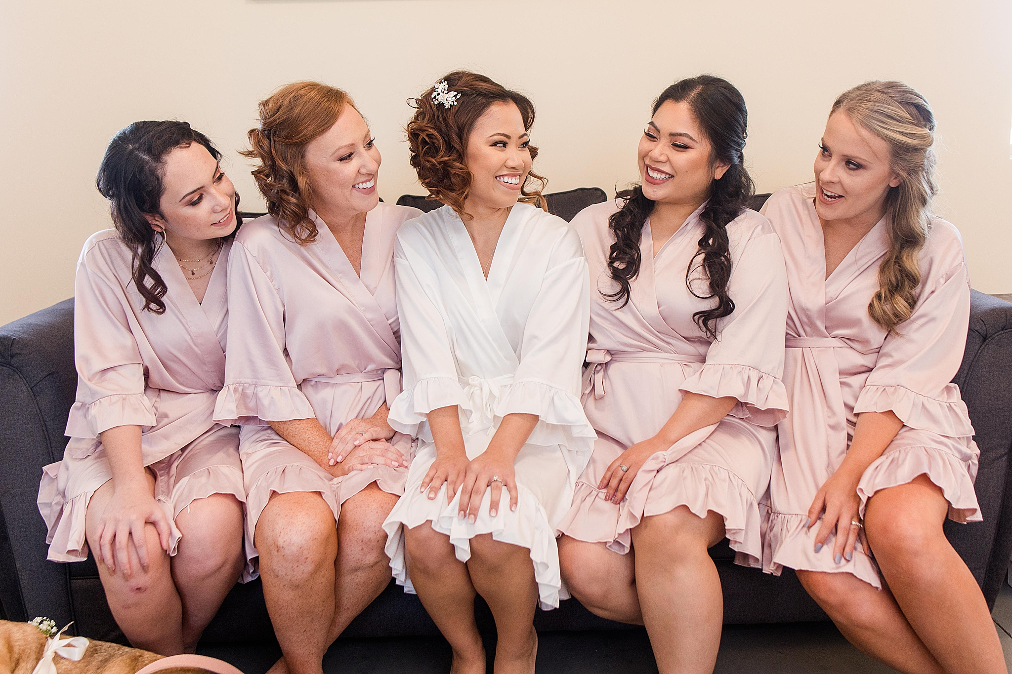 bride poses with bridesmaids in pink robes