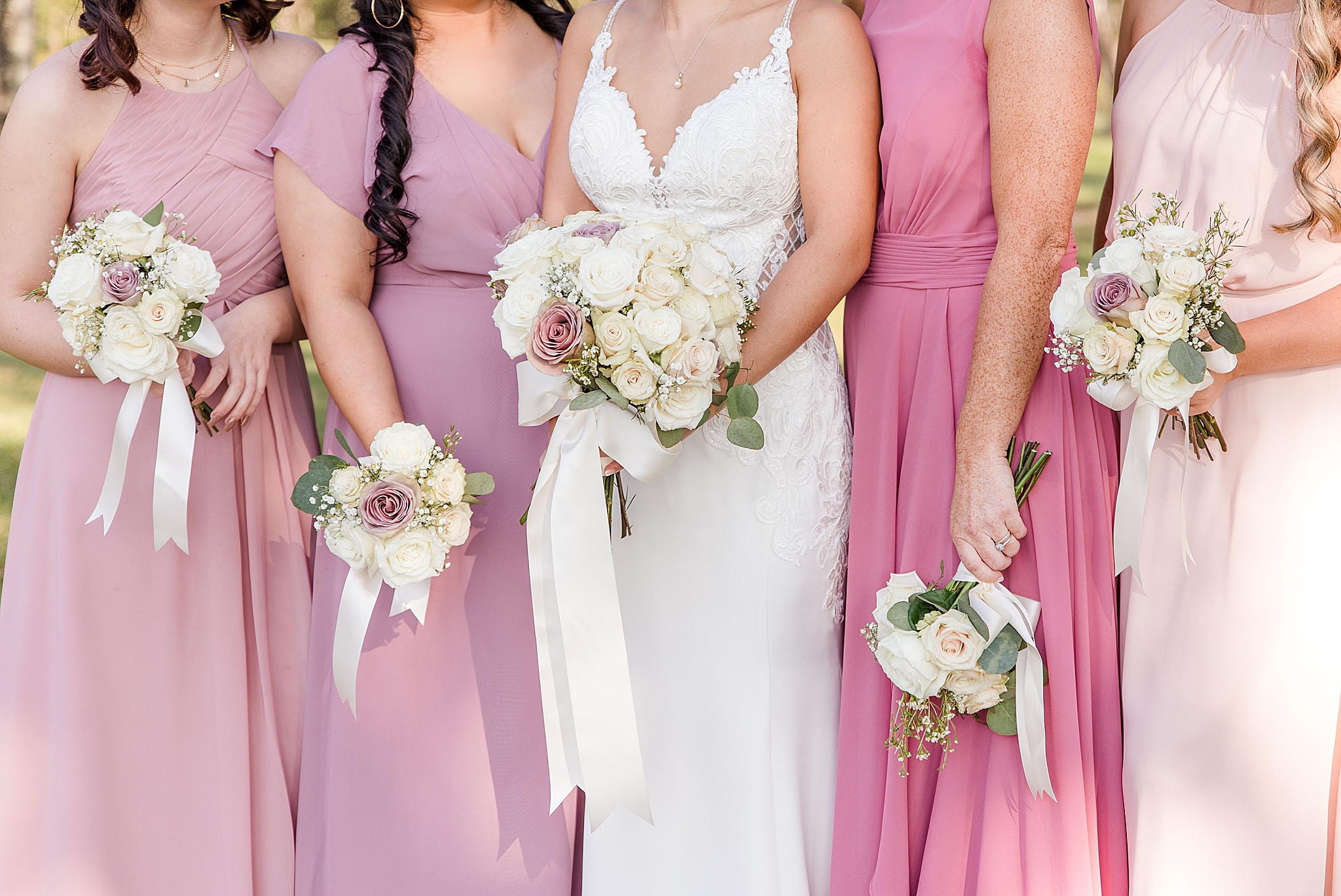 bridesmaids in mismatched pink gowns hold flowers