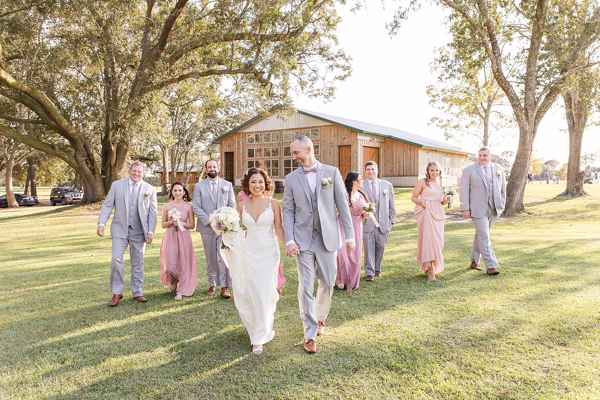 bride and groom hold hands walking with wedding party