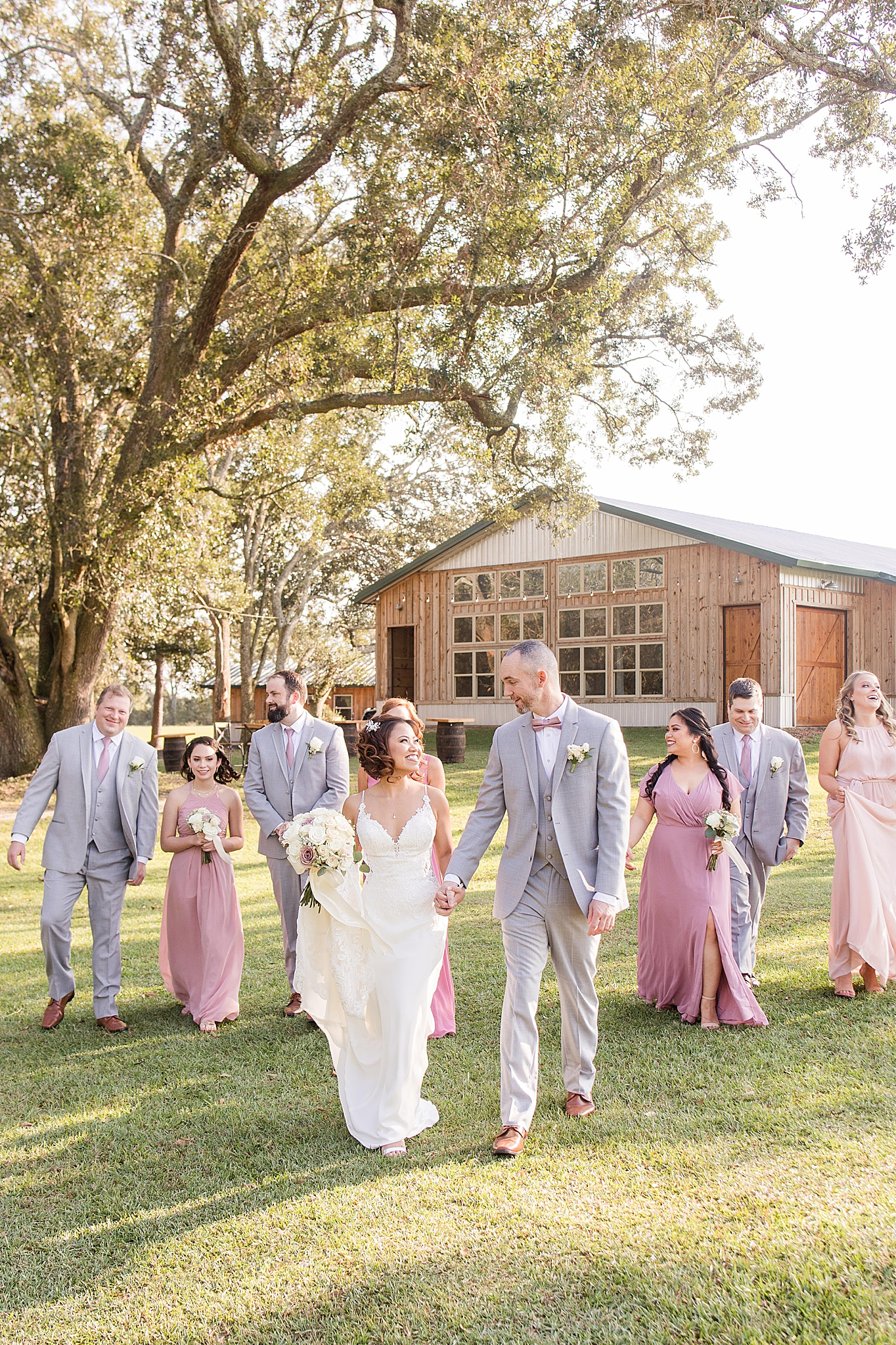 bride and groom walk with bridal party outside at the Orchard at Hayes Farm