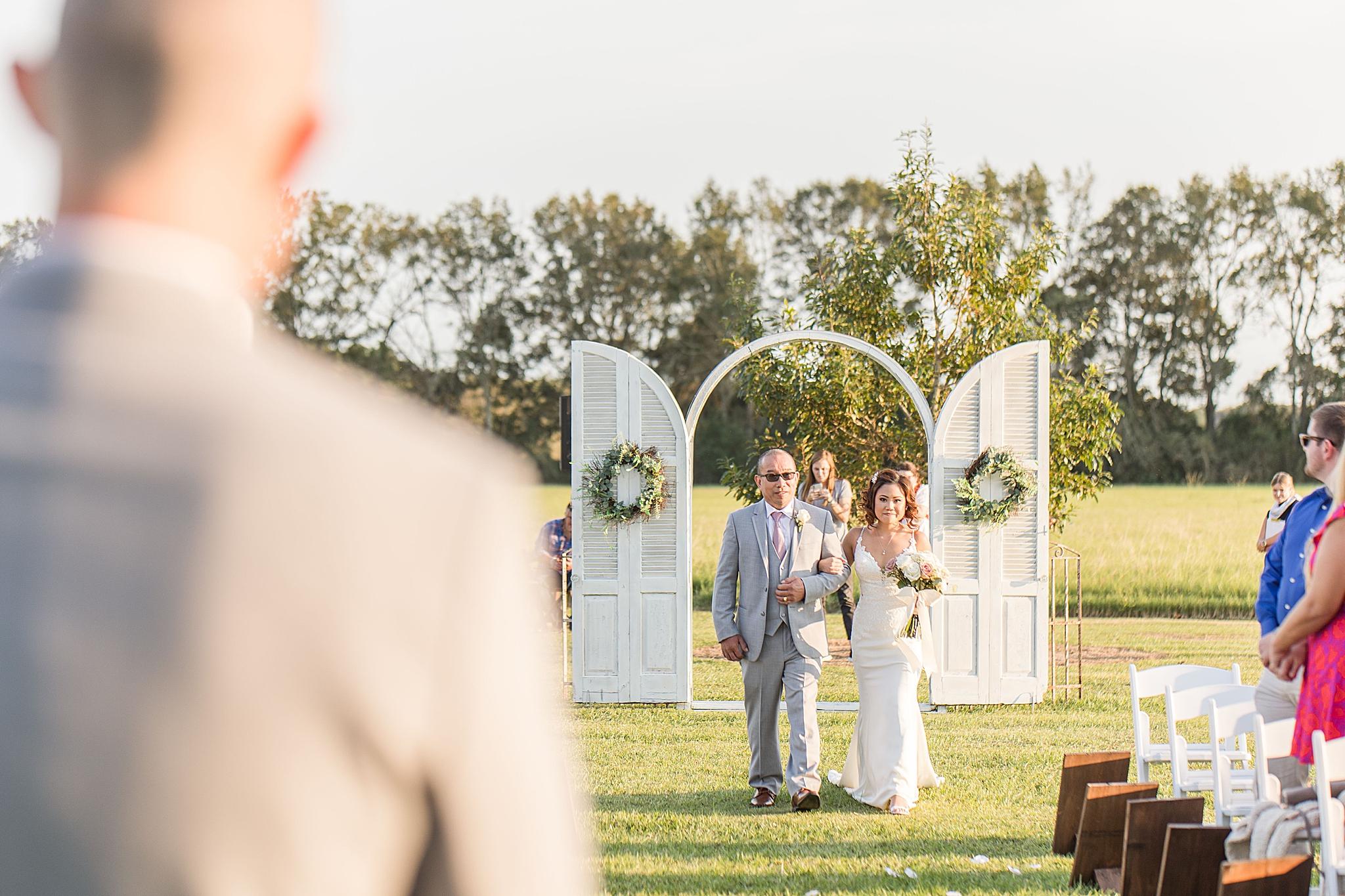 bride walks down aisle at Orchard at Hayes Farm