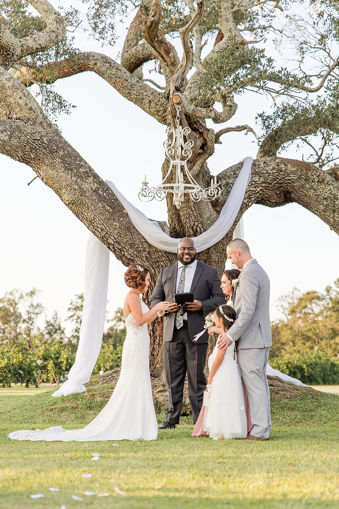 bride and groom exchange vows with daughters as a family