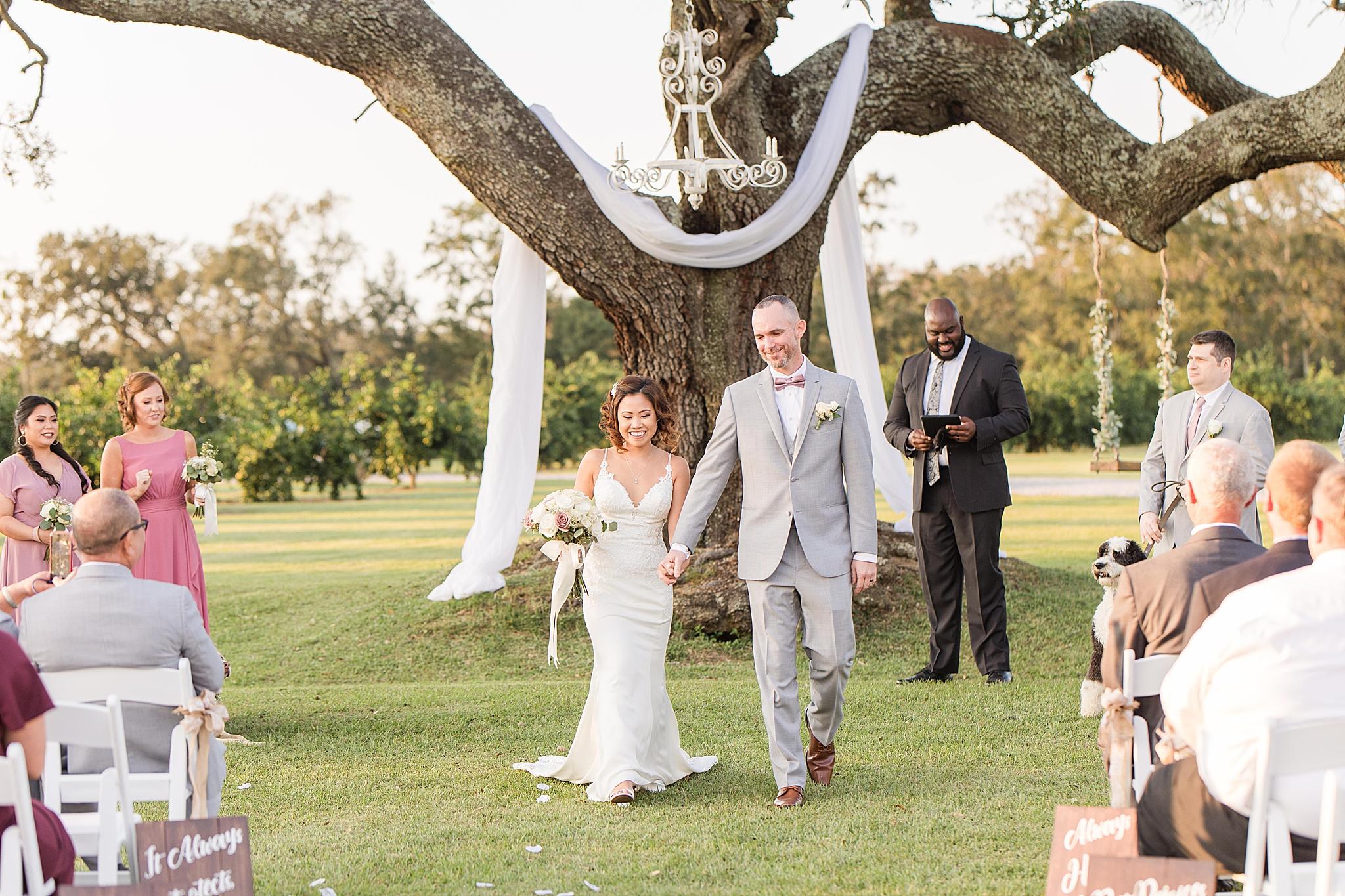 bride and groom walk up aisle at Orchard at Hayes Farm