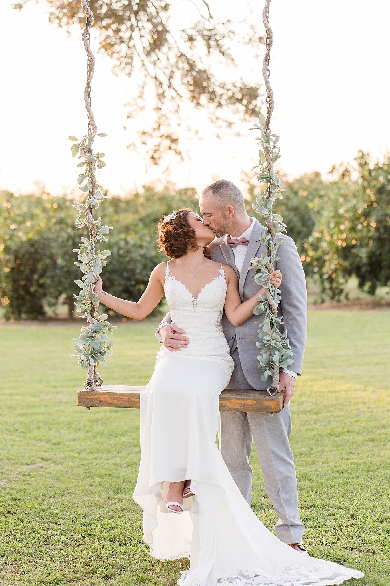 bride and groom kiss while bride sits on wooden swing