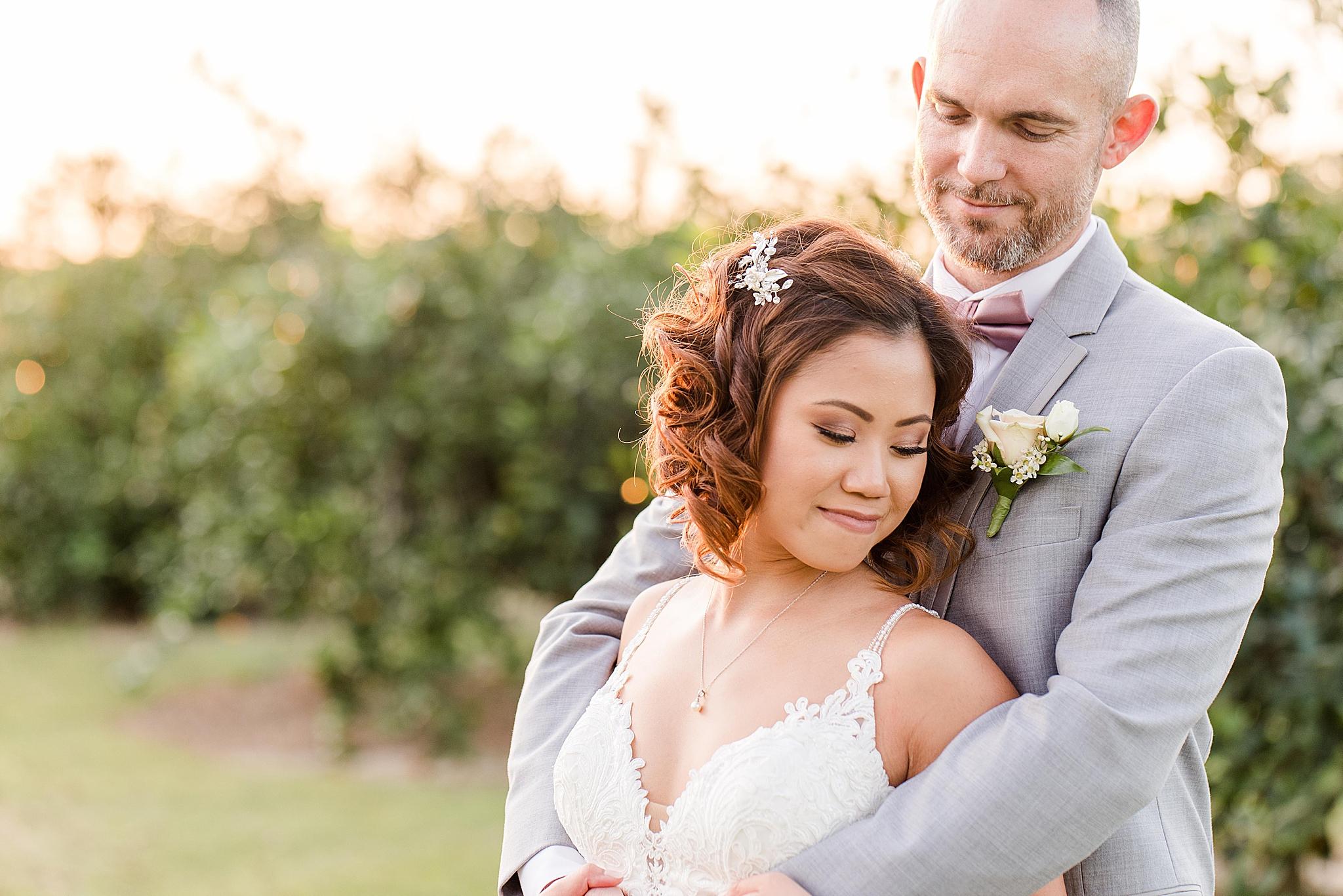 groom hugs bride from behind during AL wedding portraits