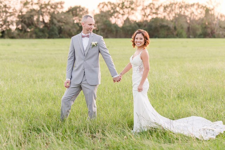 bride and groom walk through field at sunset