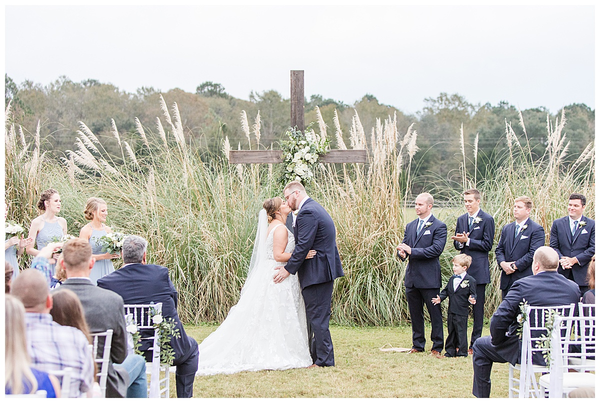 groom kisses bride by wooden cross during Laurel Hill Farm wedding ceremony