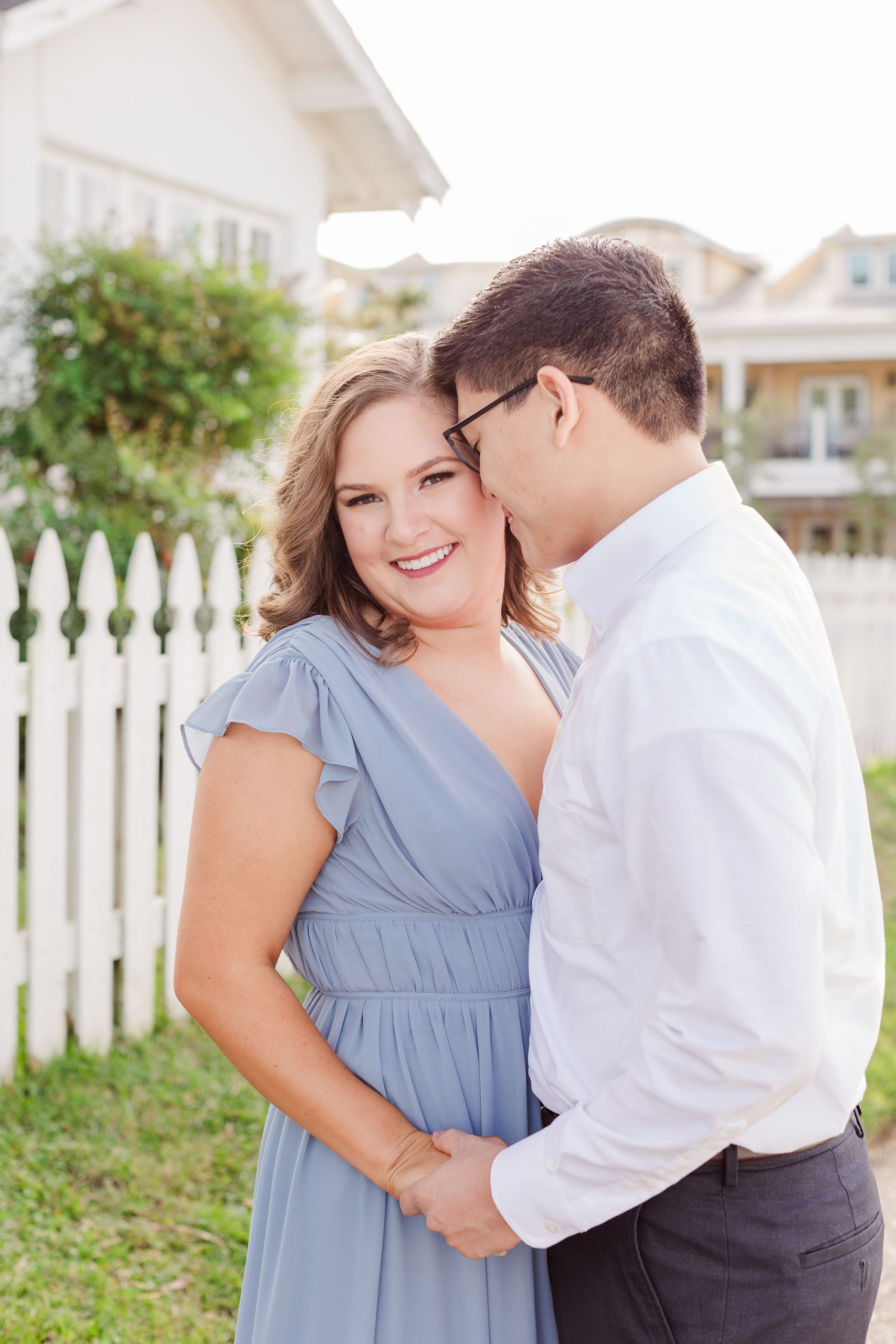 groom nuzzles bride's forehead during Downtown Fairhope engagement portraits