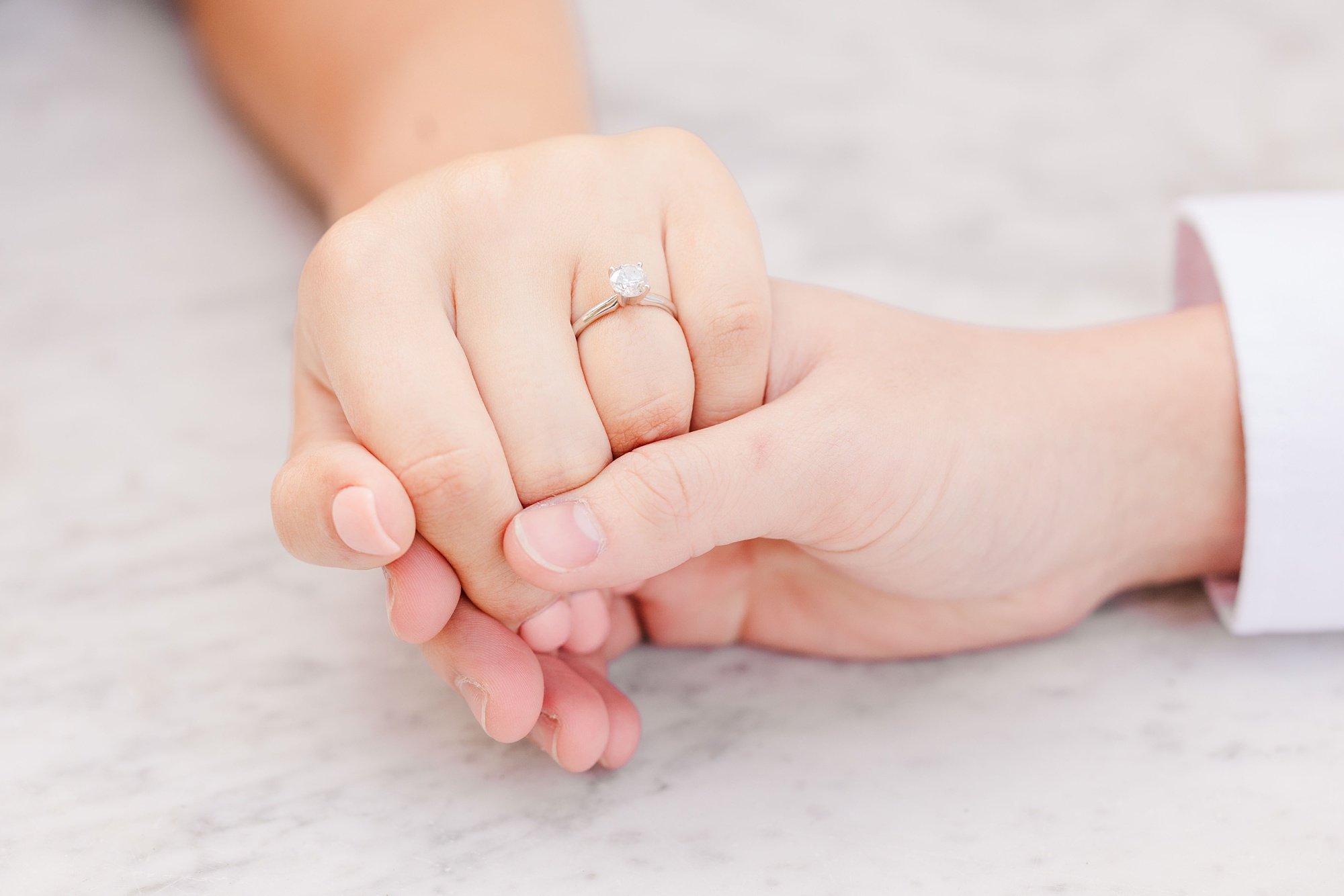 bride and groom hold hands showing off engagement ring