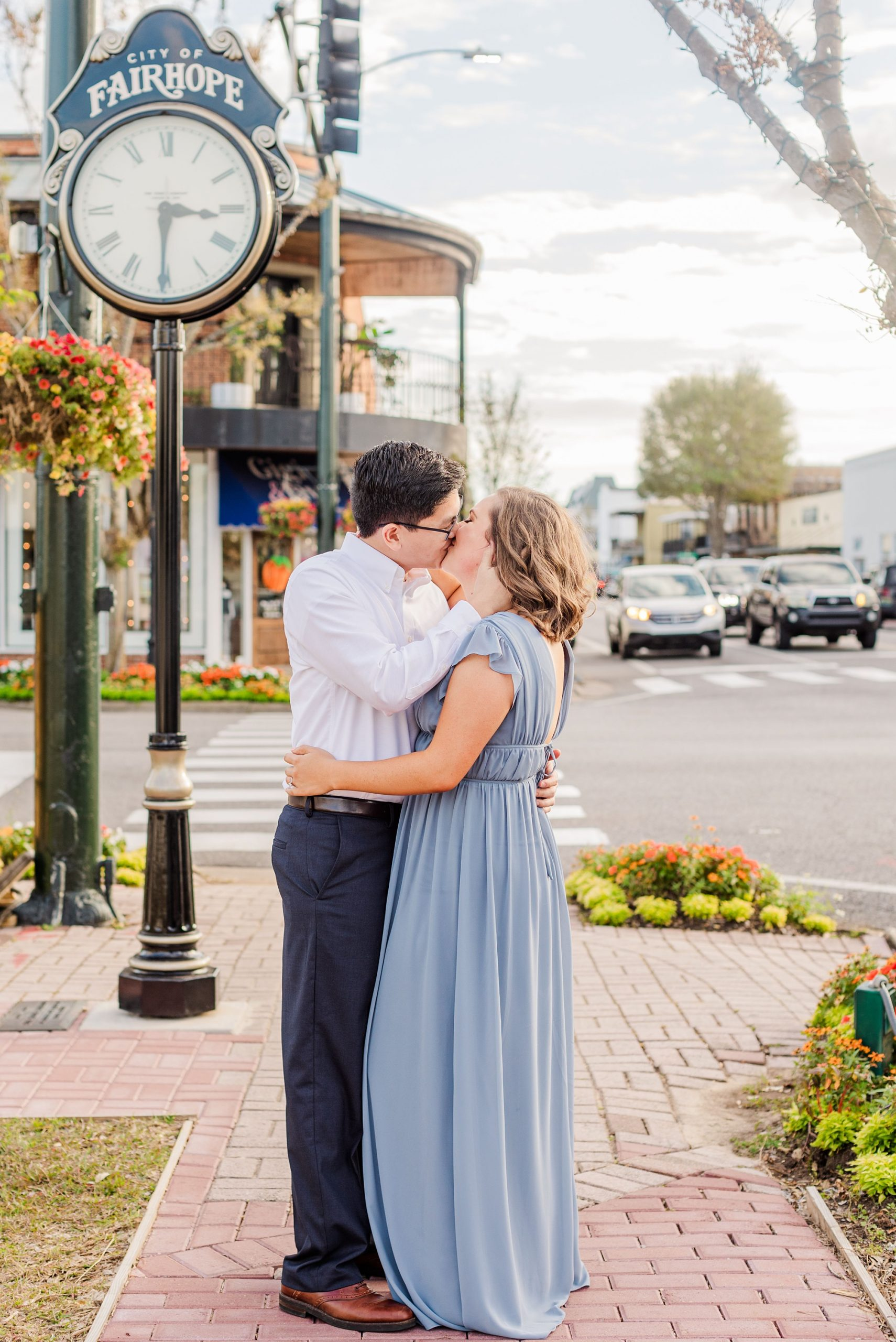 engaged couple kisses by antique street clock