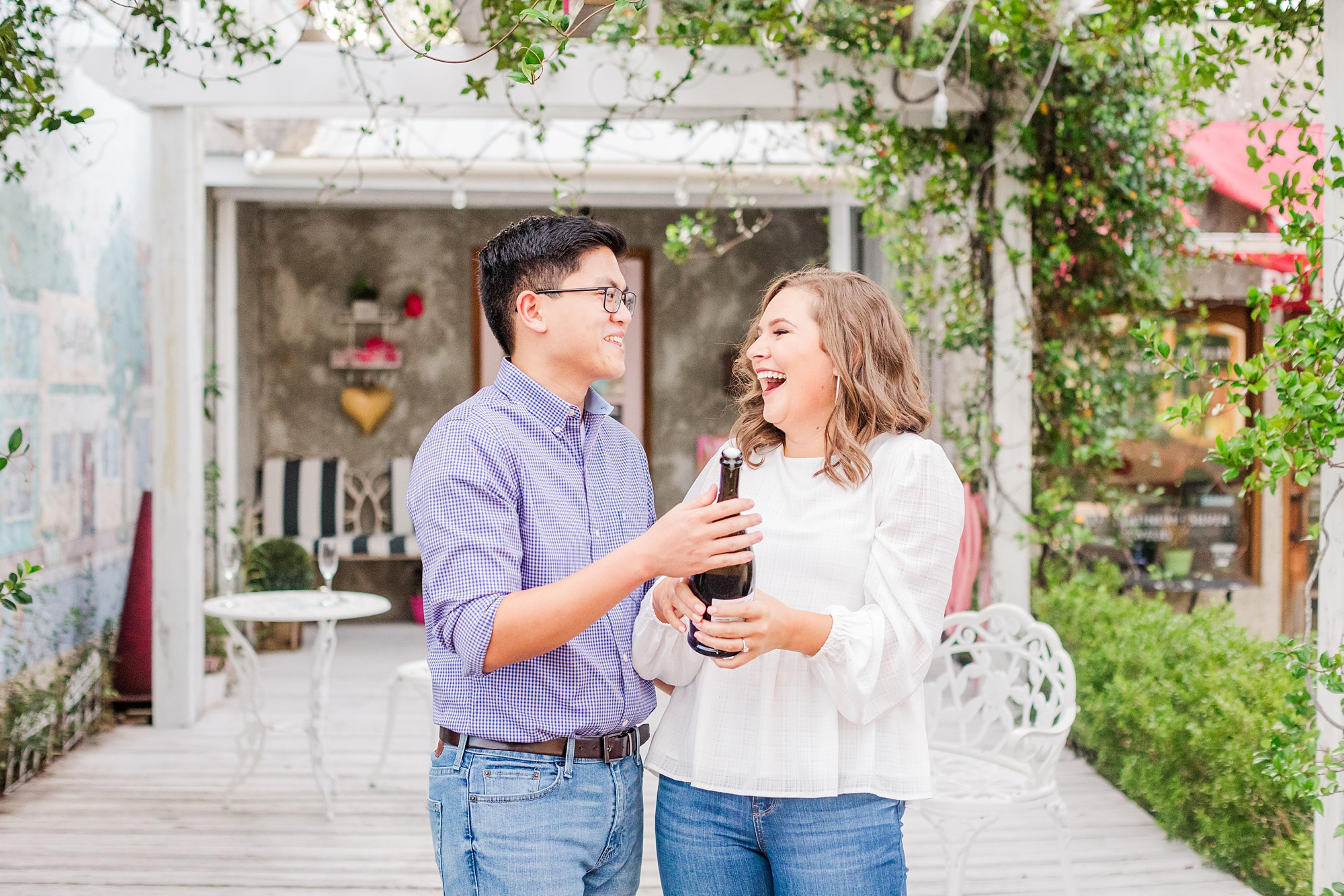bride and groom pop champagne during AL engagement photos