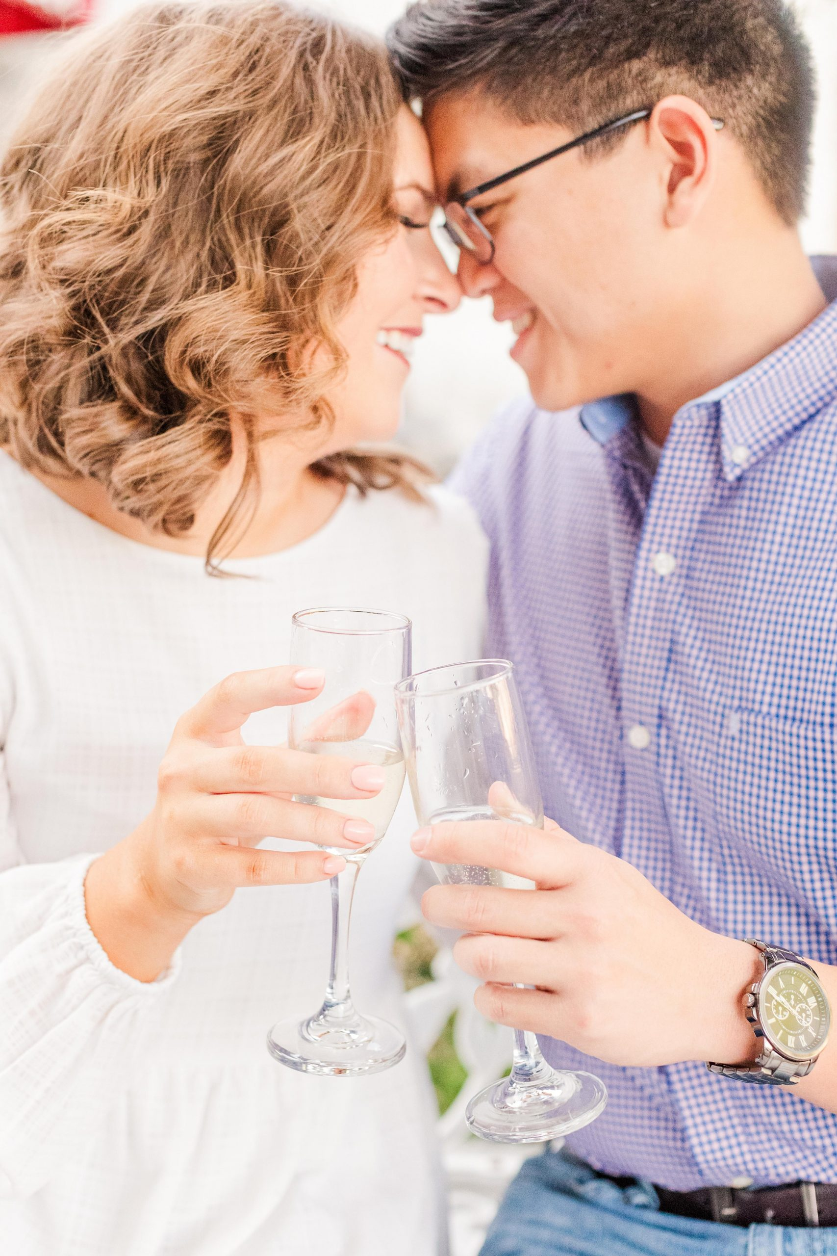 bride and groom touch noses while toasting with champagne
