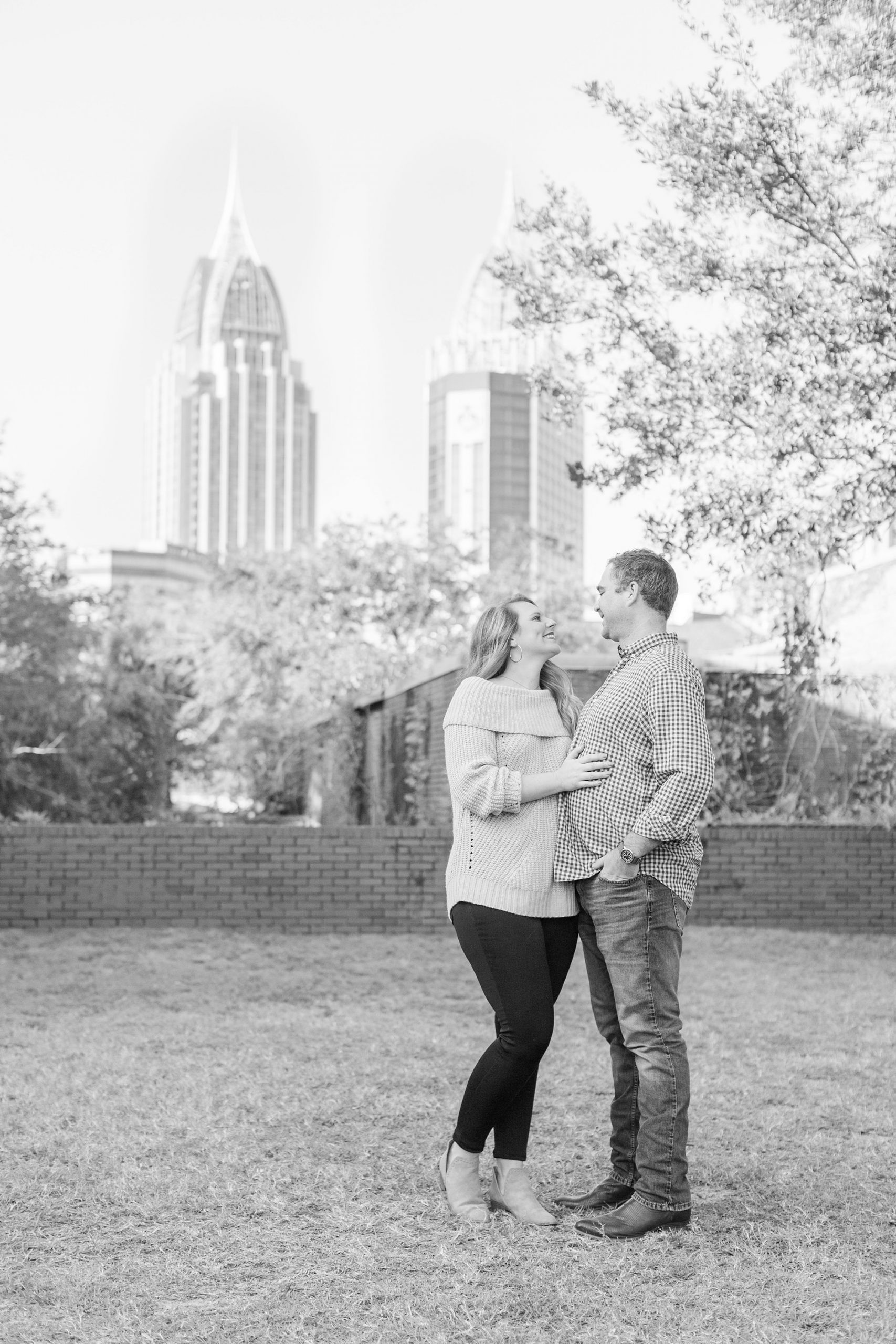 couple poses in front of Mobile AL skyline