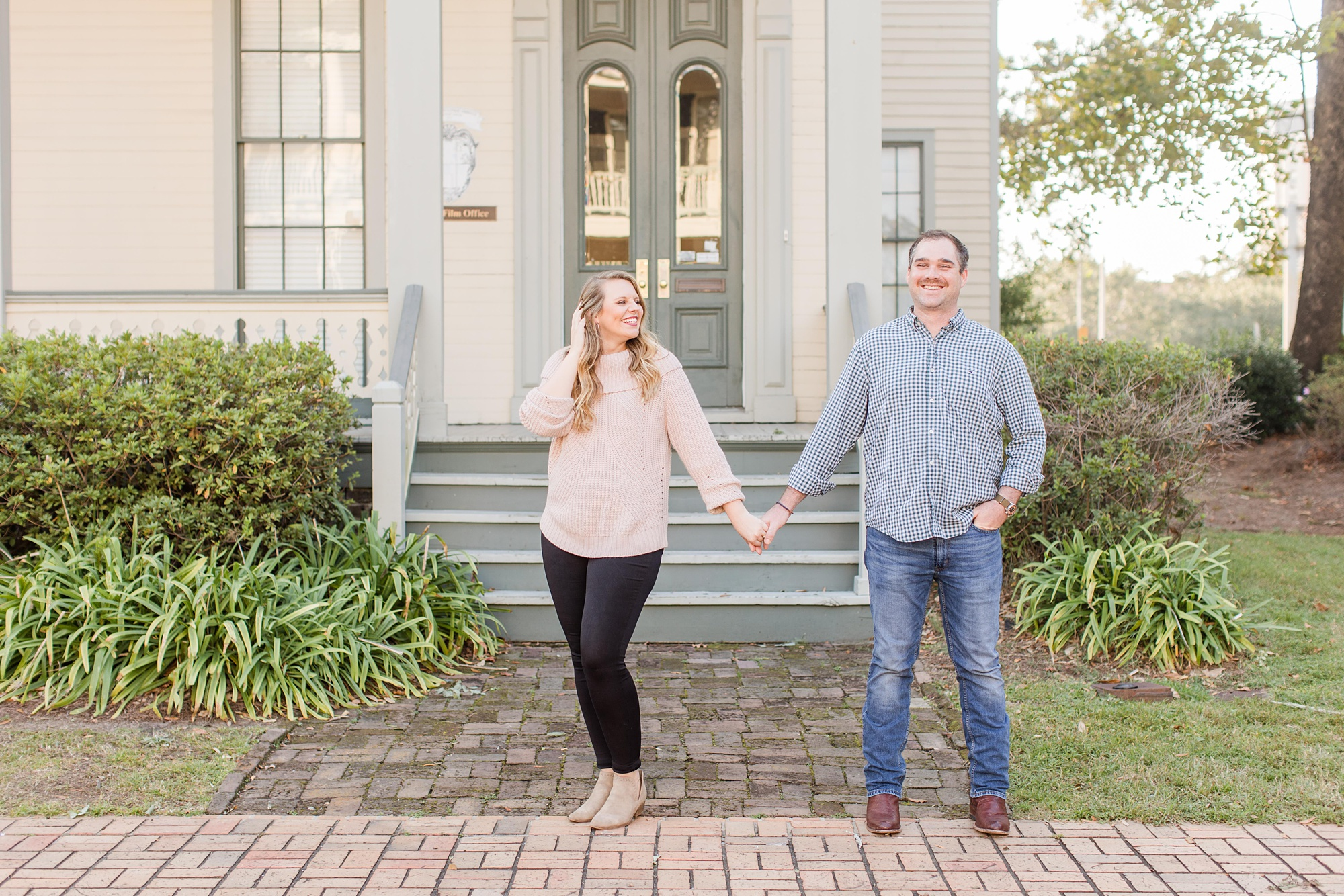 couple poses by front steps of Fort Conde Inn