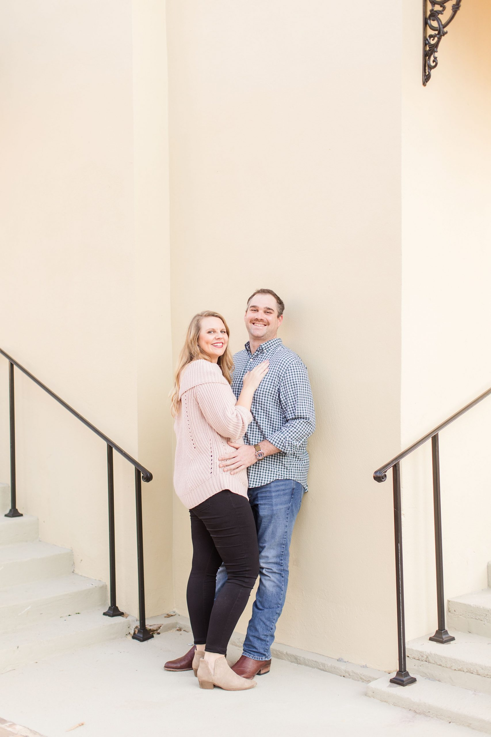 bride and groom pose between stair cases at Fort Conde Inn