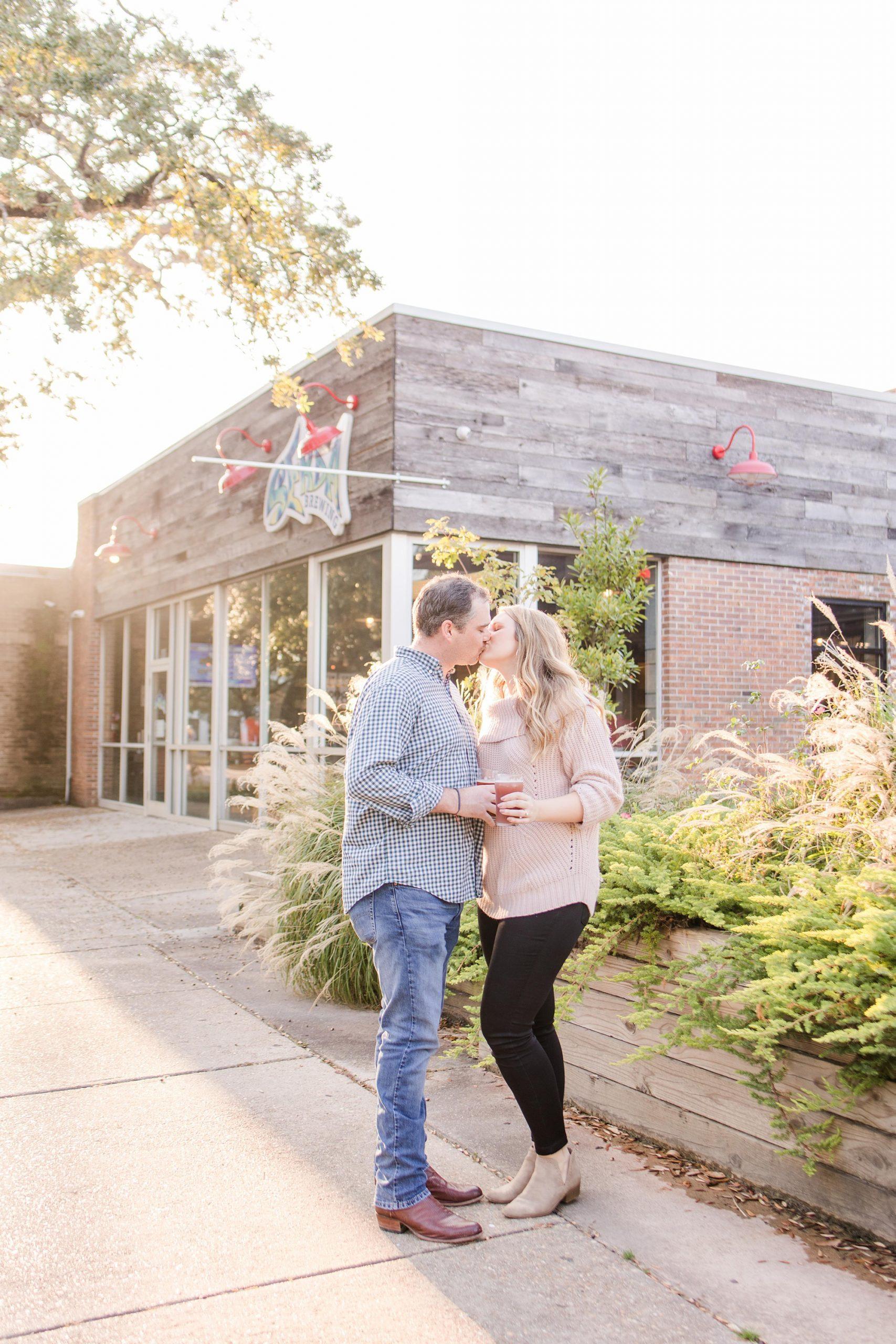engaged couple kisses outside Serda Brewing