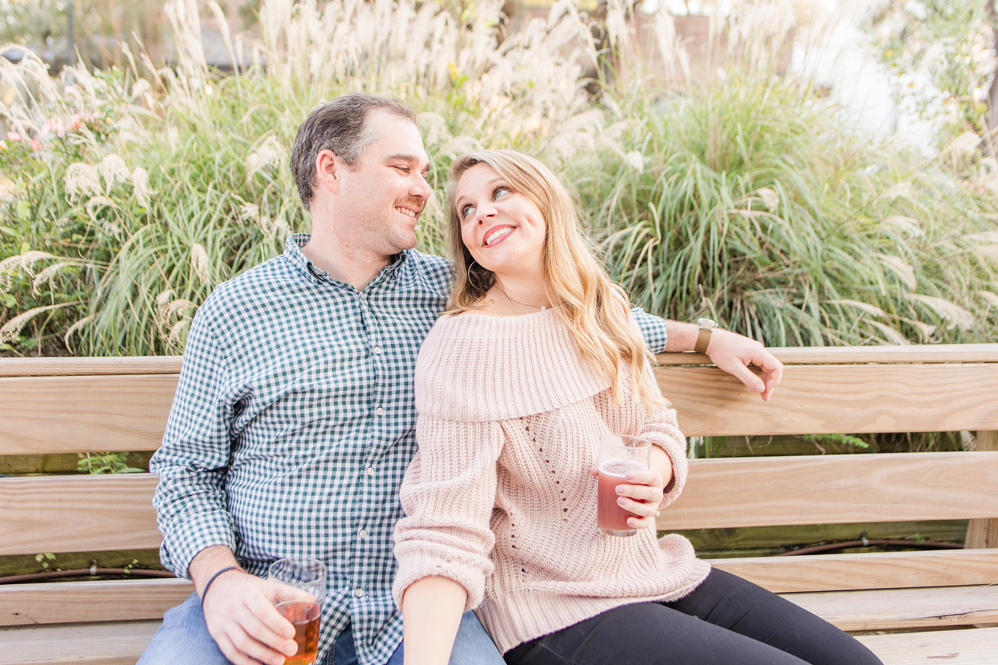 bride and groom sit on bench with beers at Serda Brewing