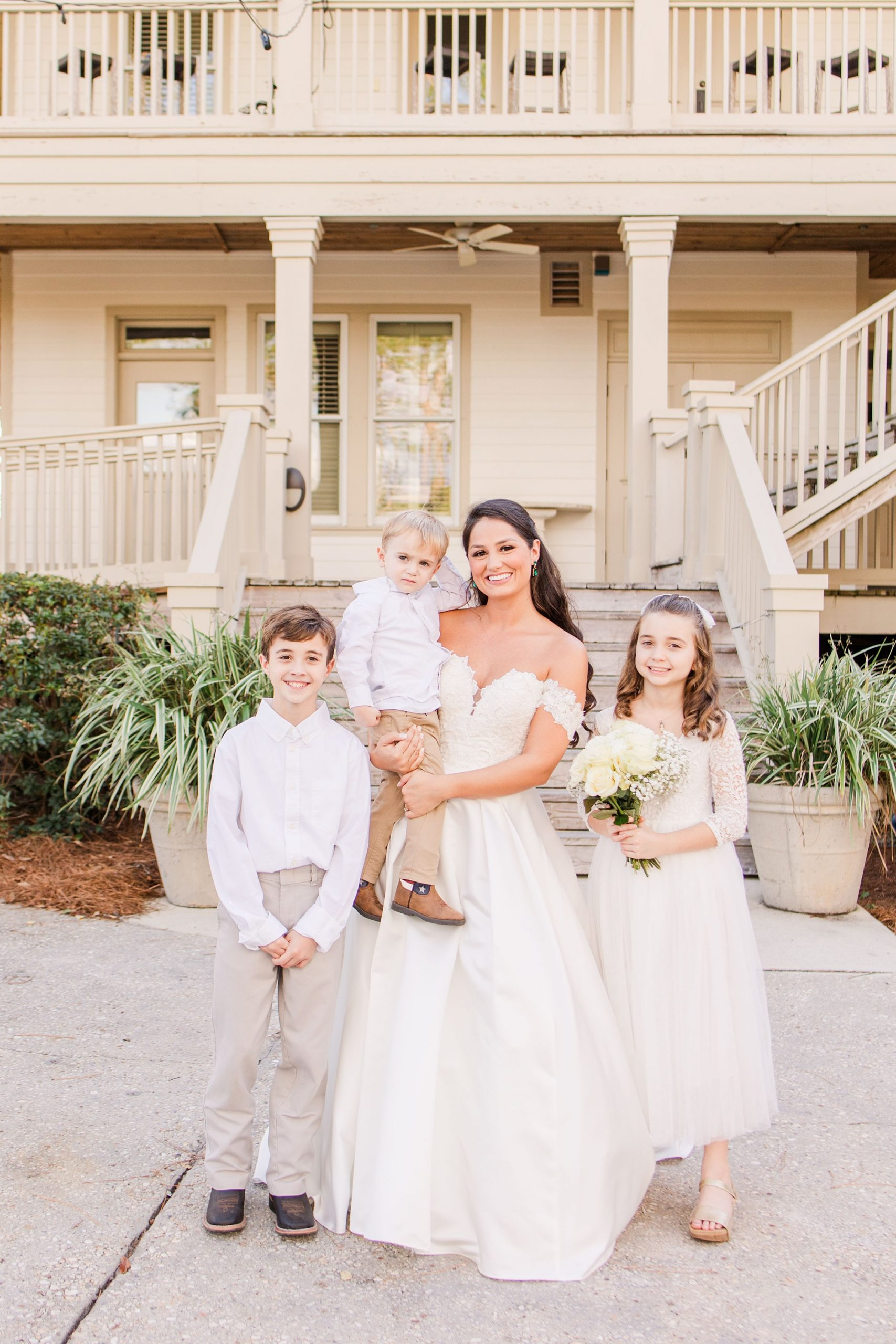 bride poses with flower girl and ring bearers