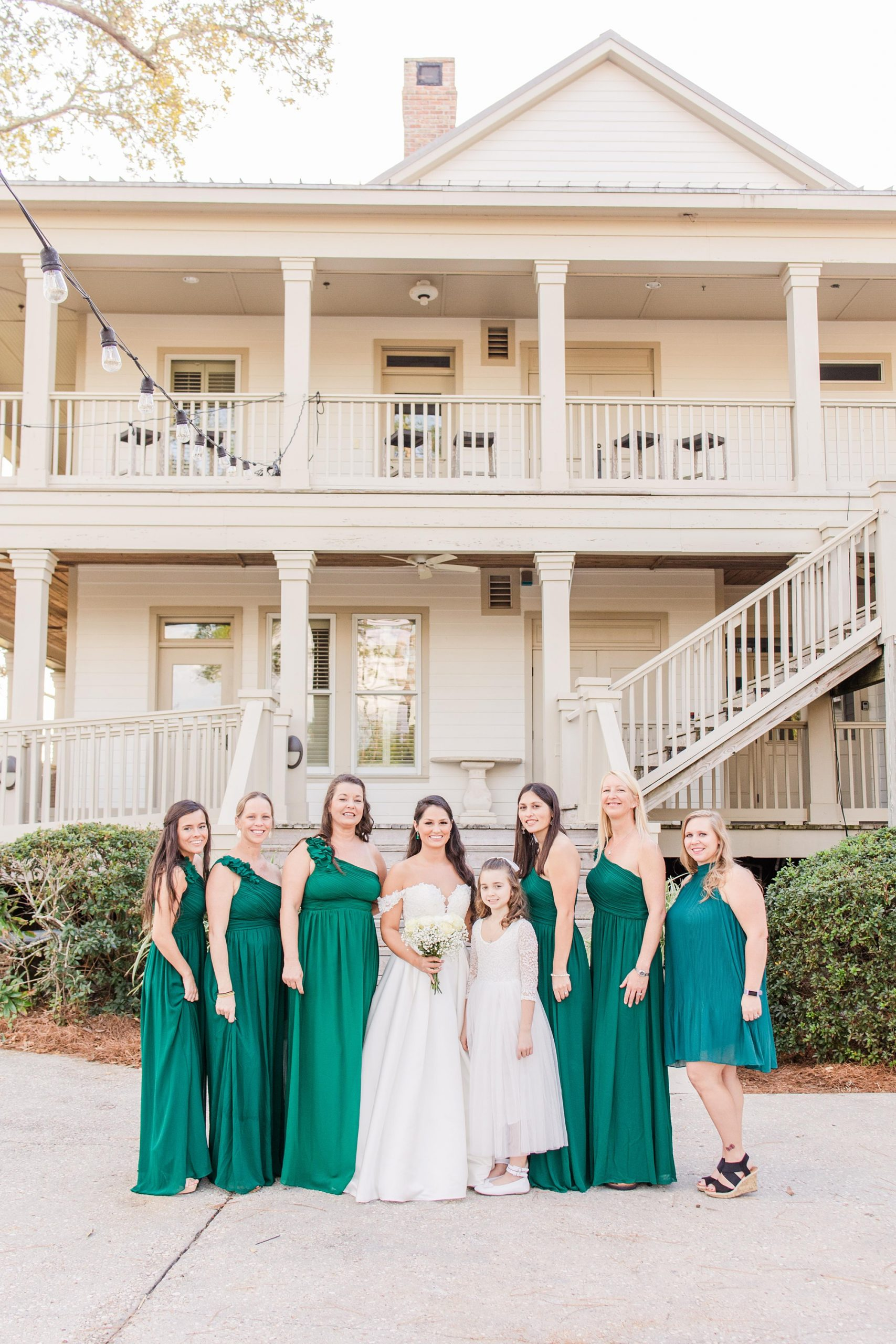bride poses with bridesmaids in emerald green dresses