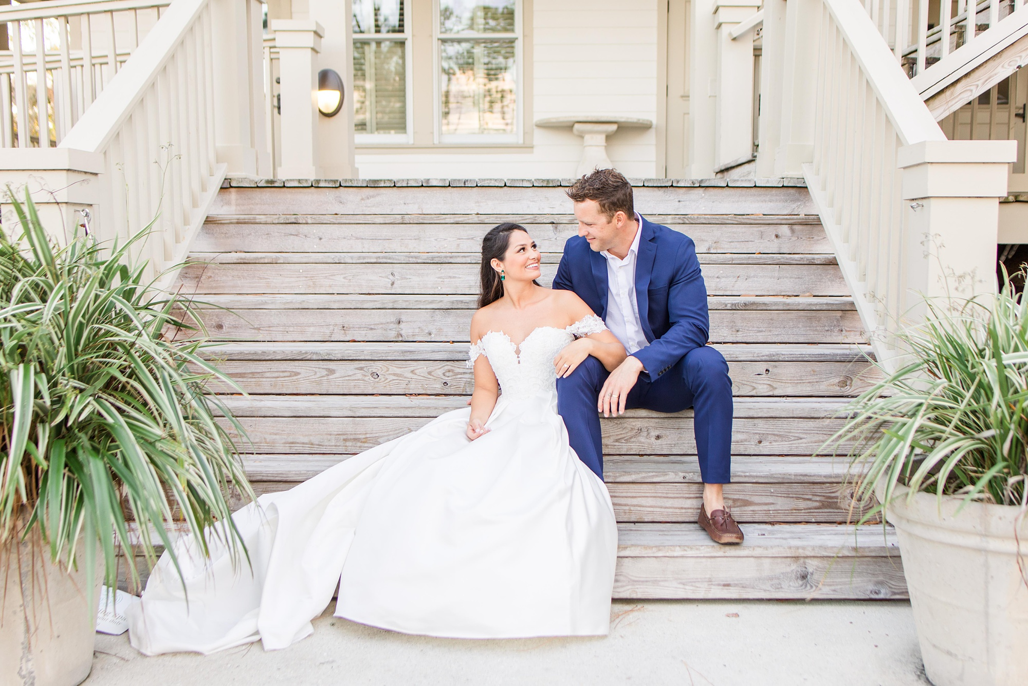 bride and groom sit on steps at Heron Pointe at the Wharf