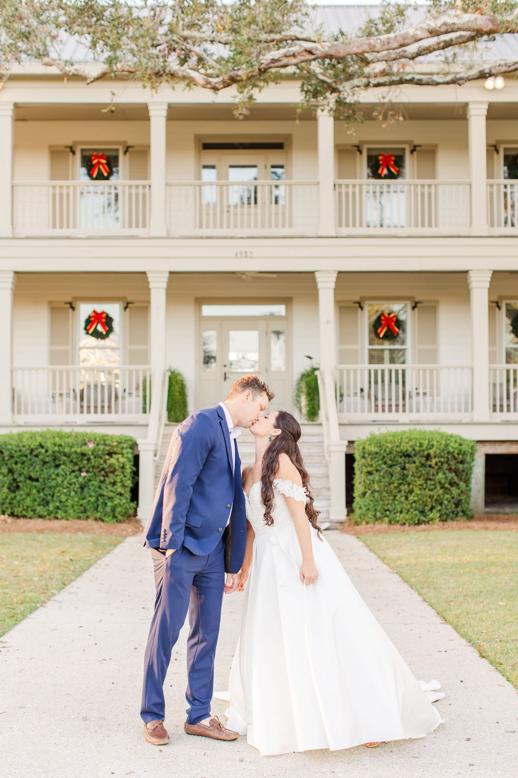 bride and groom kiss outside Heron Pointe at the Wharf