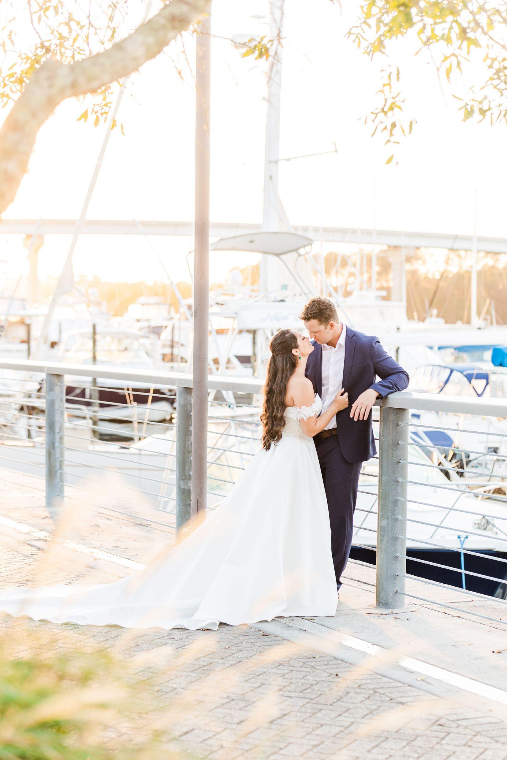 bride and groom pose by Orange Beach marina