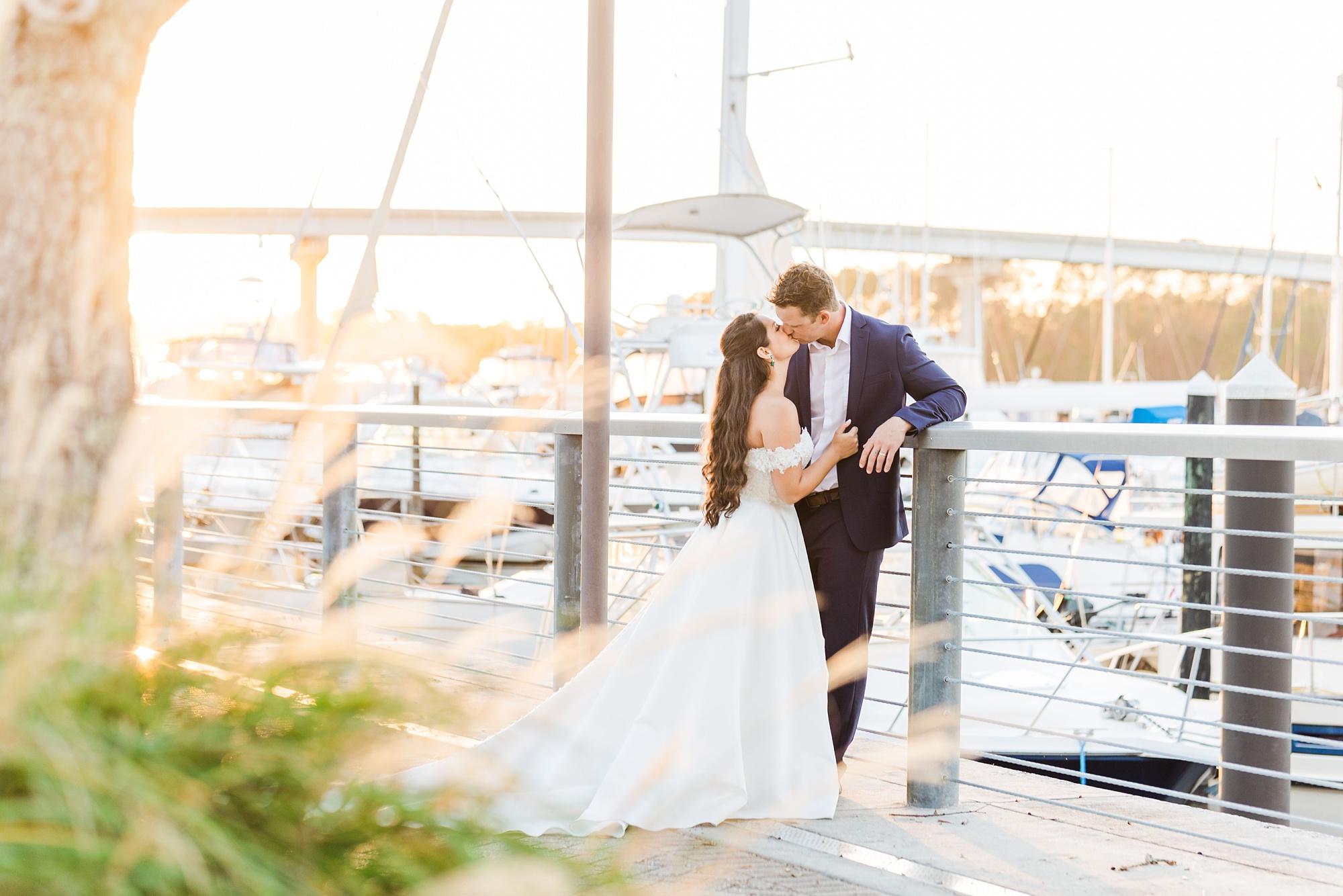 newlyweds pose on dock at Orange Beach at sunset