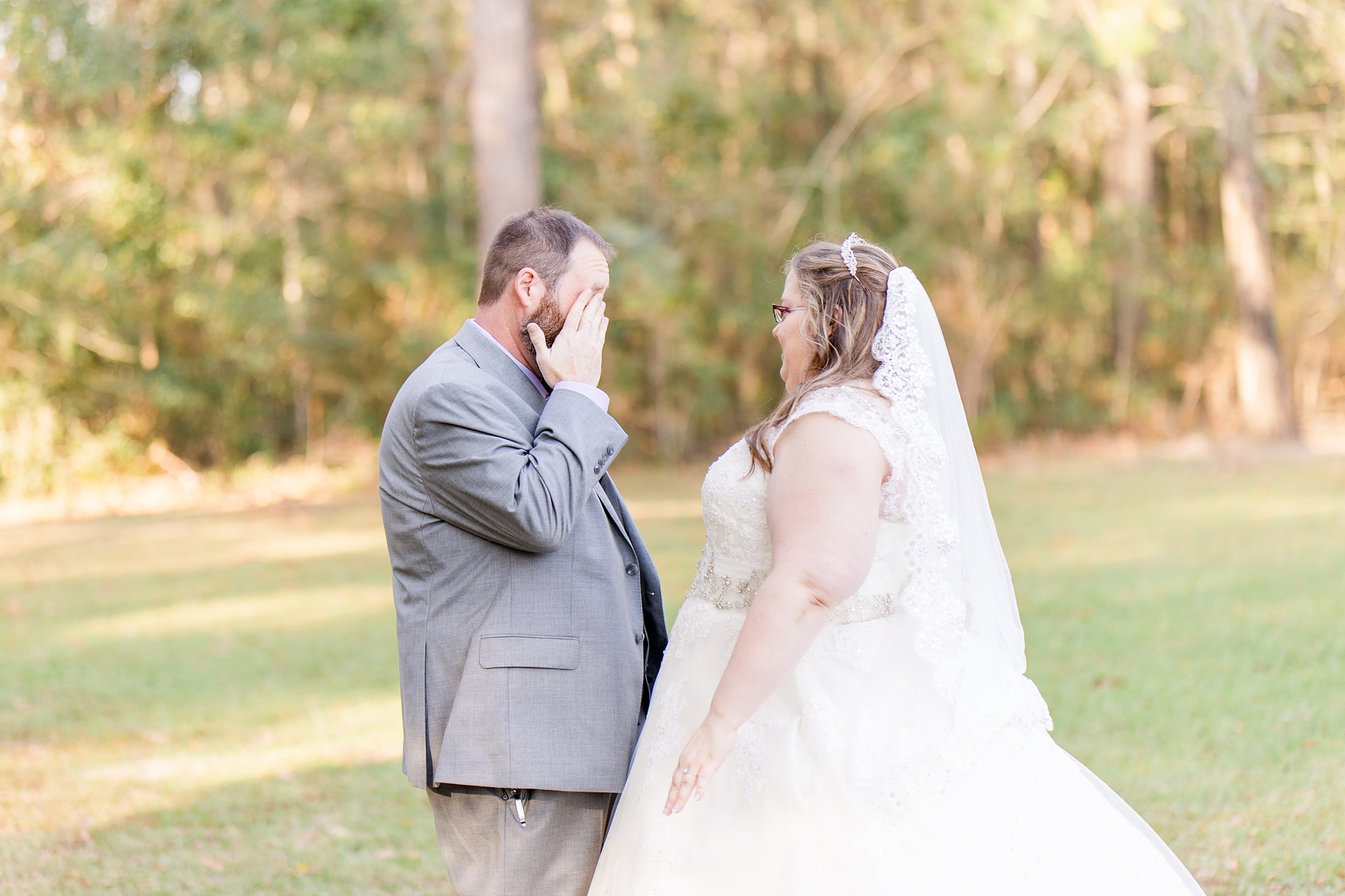 groom wipes tears from his eye during first look