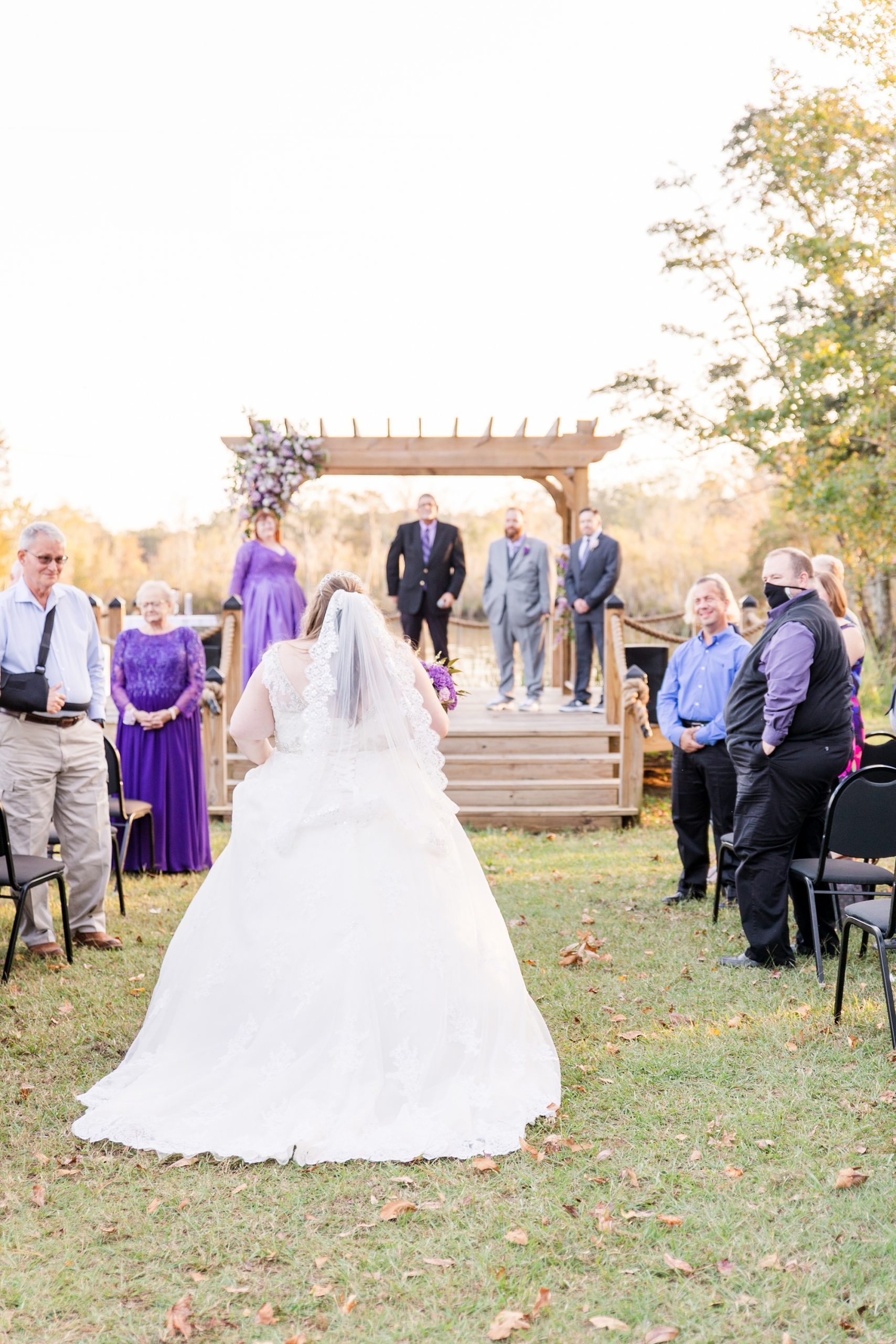 bride walks up to waterfront altar during intimate Satsuma wedding ceremony
