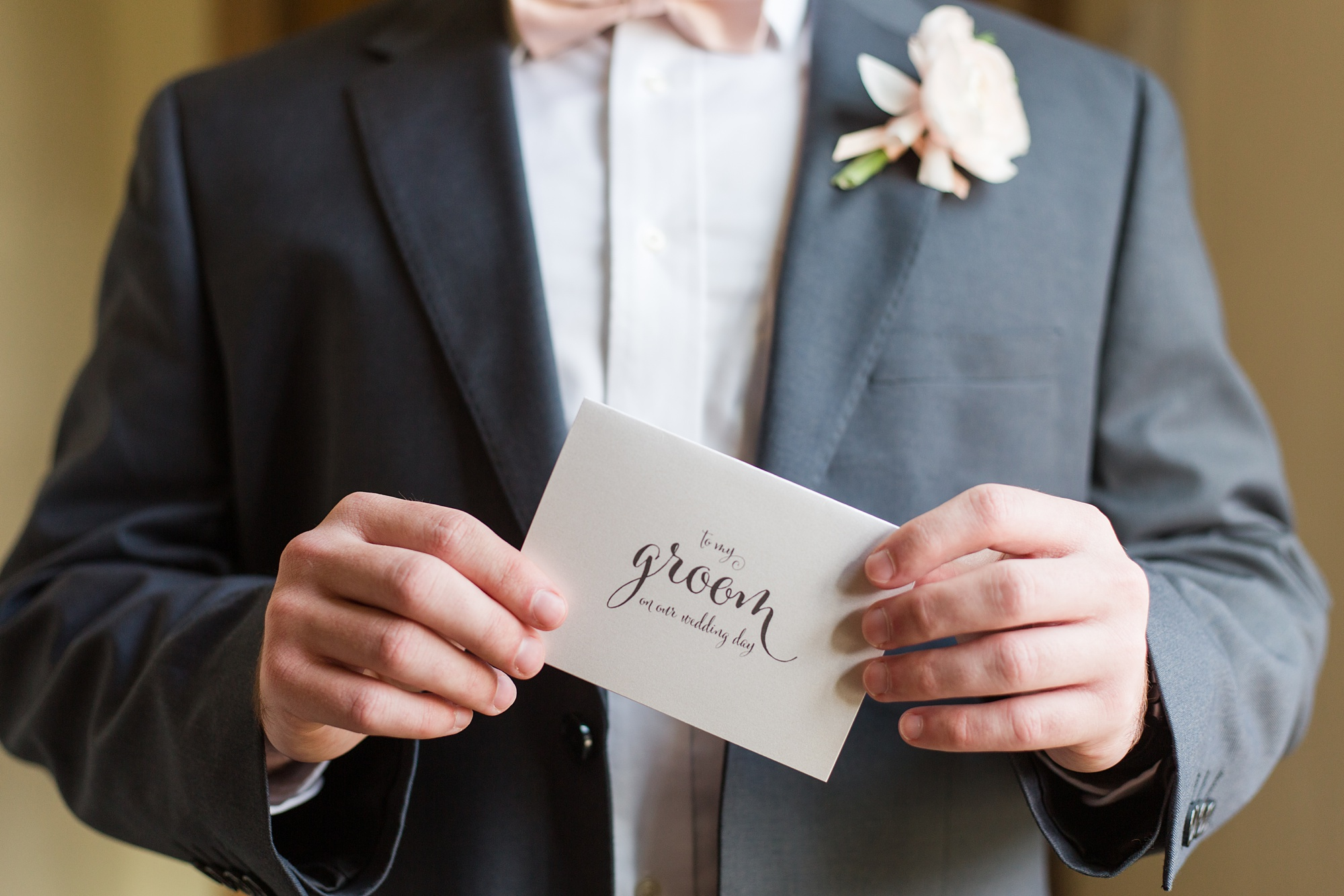 groom holds card from bride before romantic Izenstone wedding